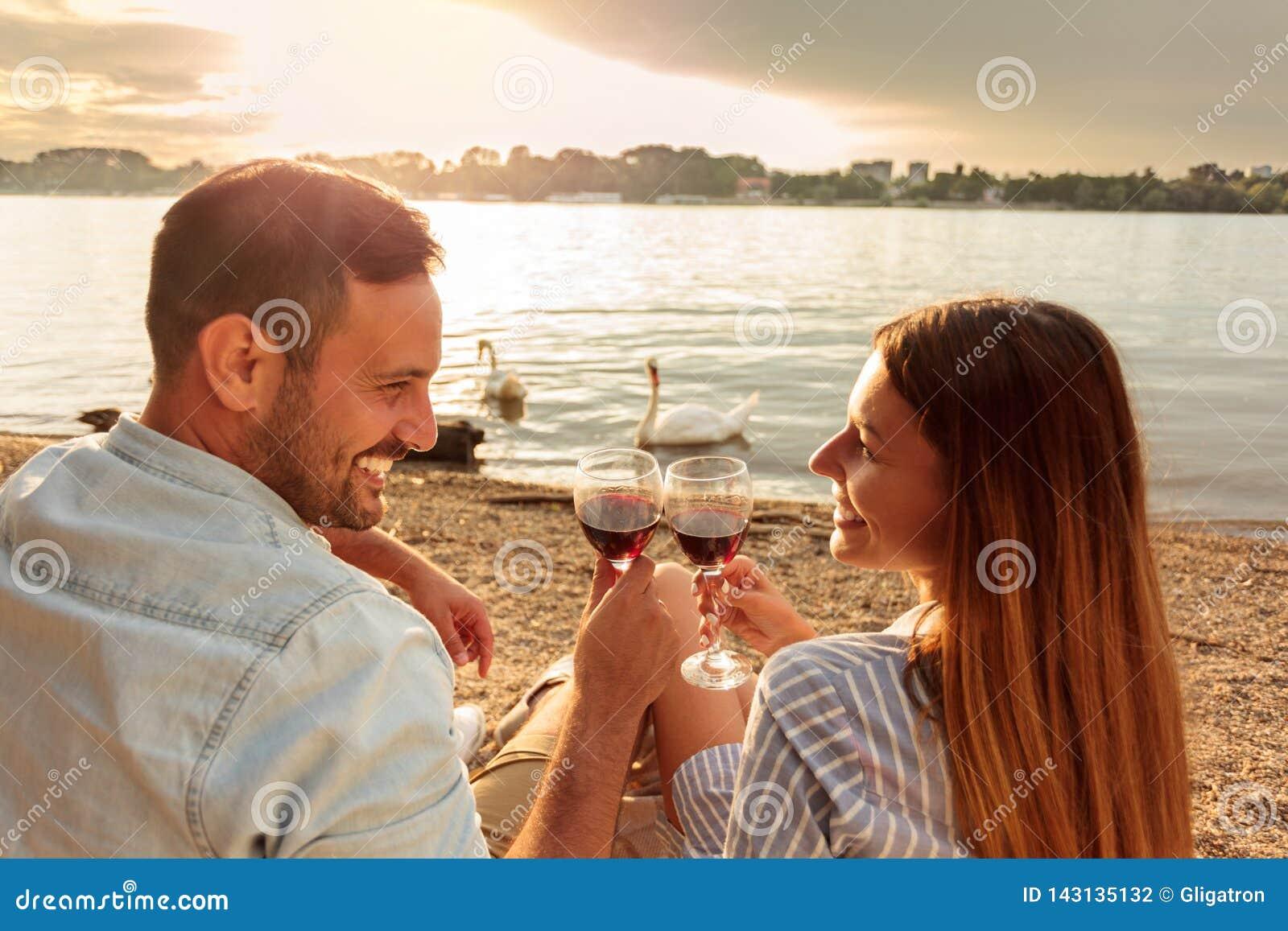 Gelukkig jong paar die een toost met rode wijn maken Het genieten van van picknick bij het strand