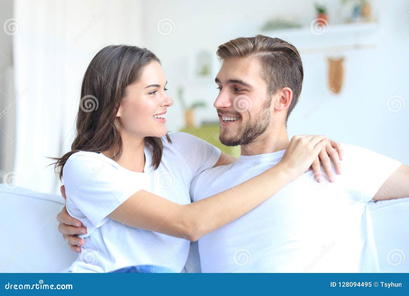 Gelukkig jong paar die en elkaar koesteren bekijken thuis binnenlands
