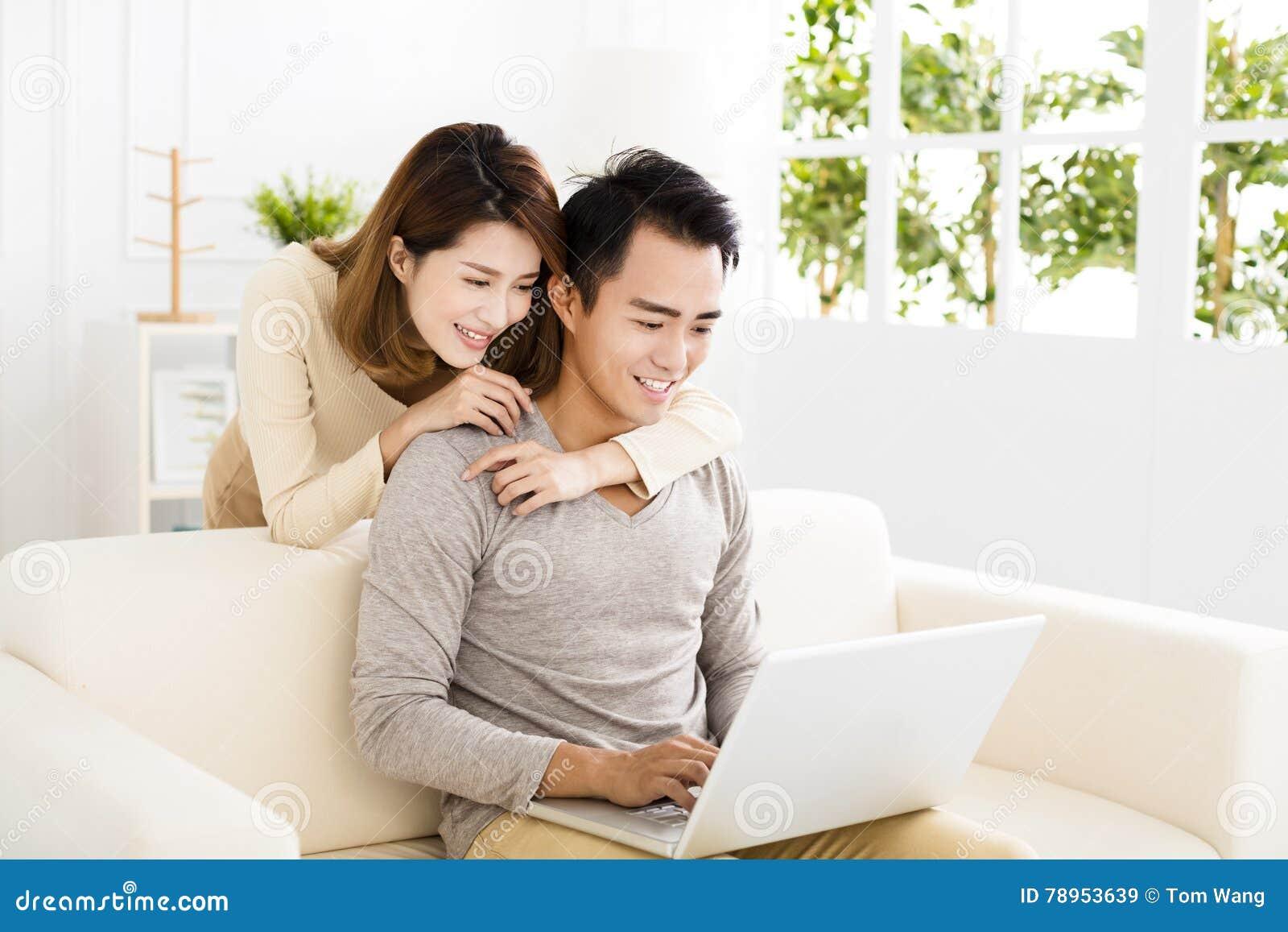 Gelukkig jong paar die laptop op bank met behulp van