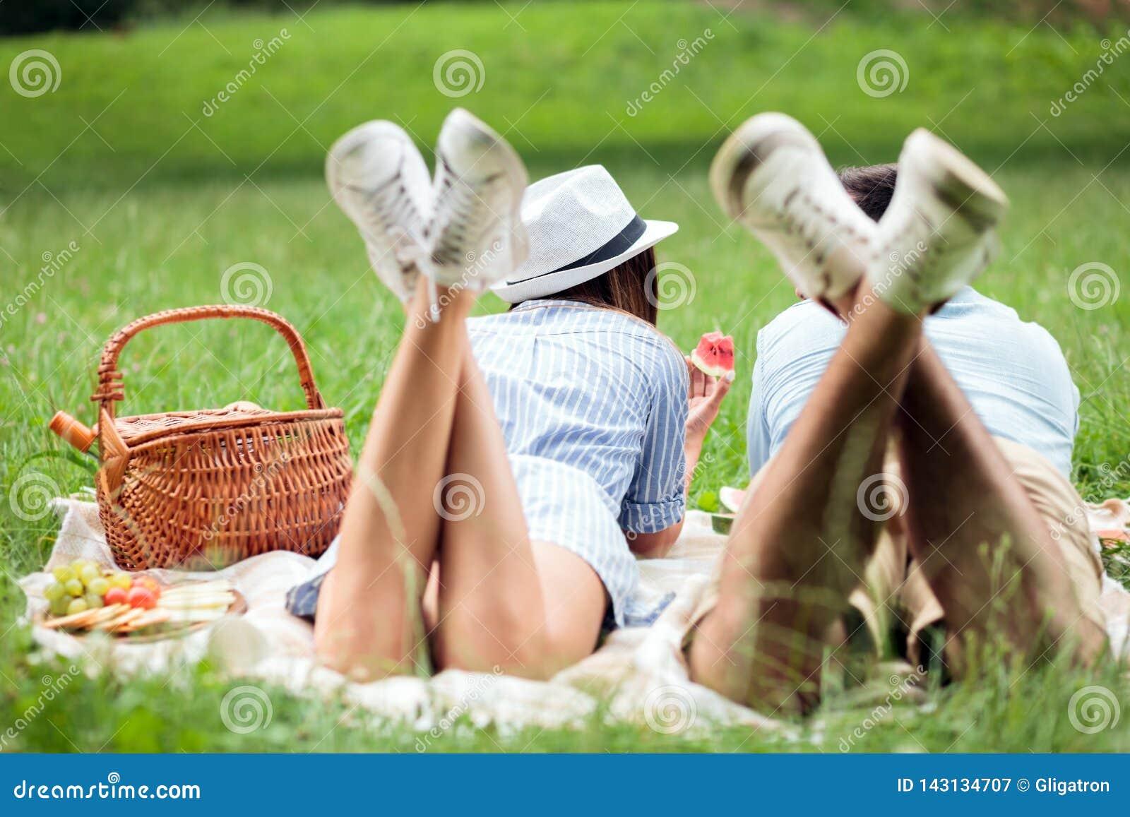 Gelukkig jong paar die naast elkaar liggen en watermeloenen, picknick in een park eten Mening van erachter