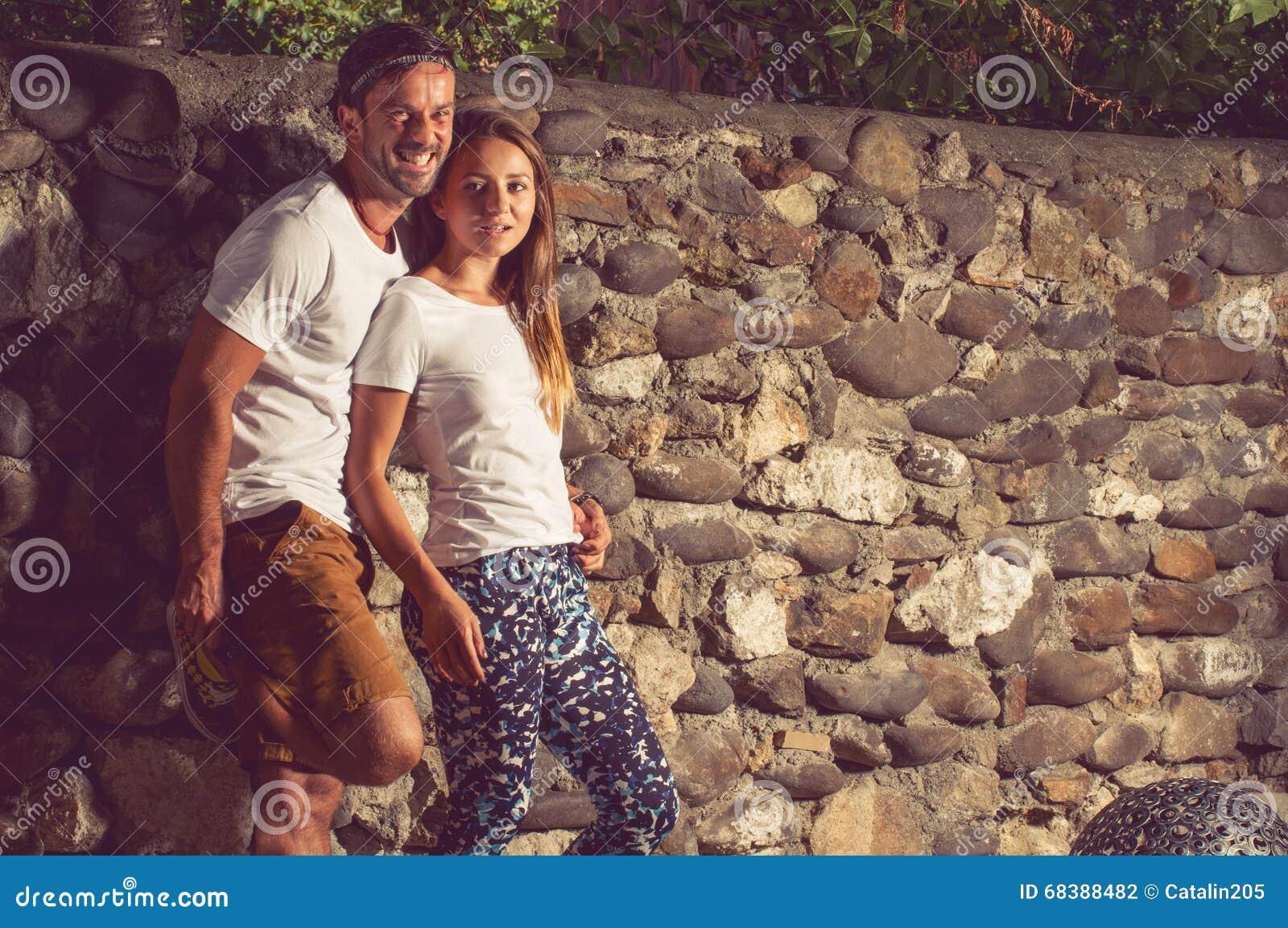 Gelukkig jong paar die openlucht dichtbijgelegen steenmuur zitten