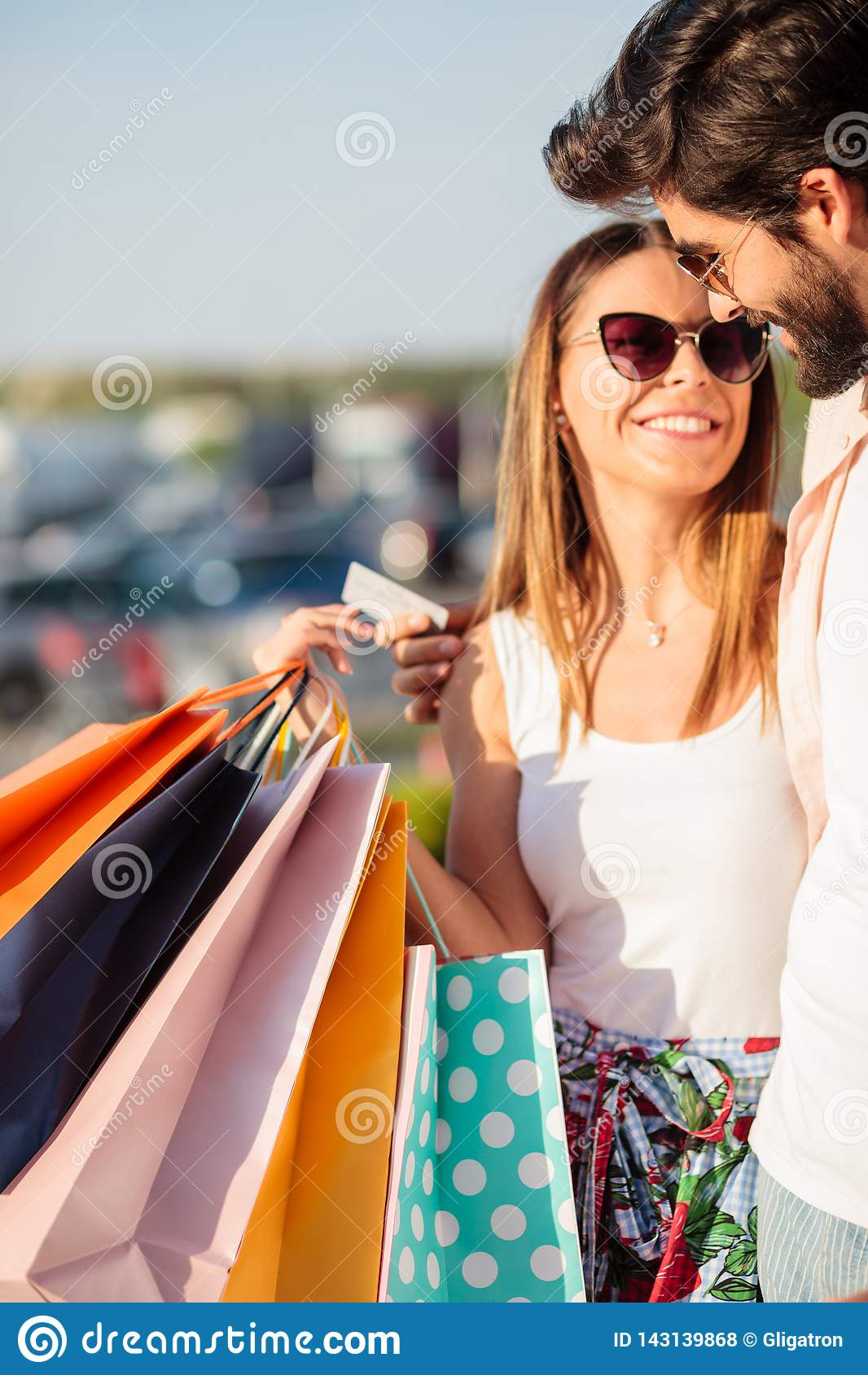 Gelukkig jong paar die van het winkelen, dragende volledige zakken terugkeren
