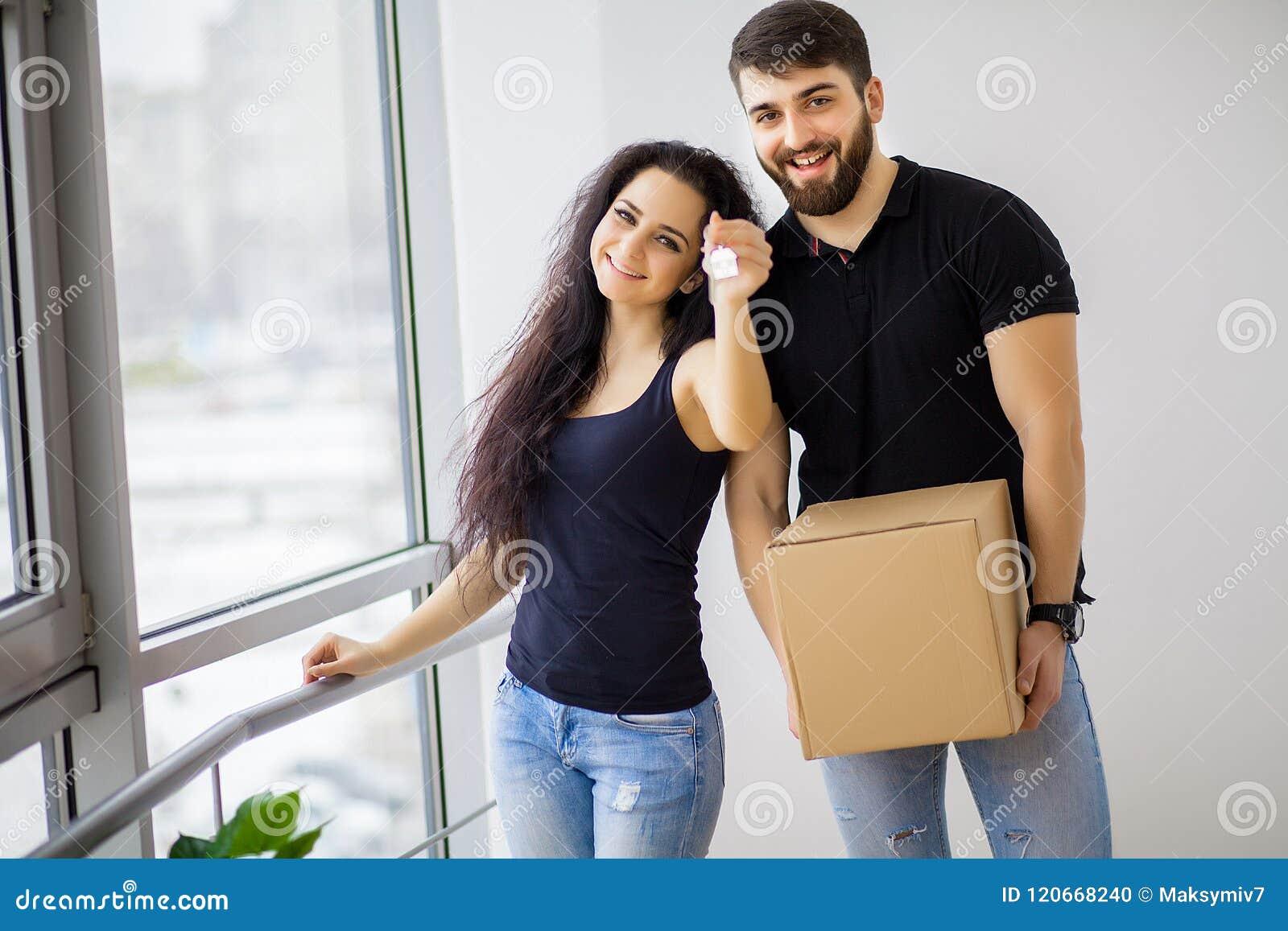 Gelukkig jong paar die zich in nieuwe huis uitpakkende dozen bewegen