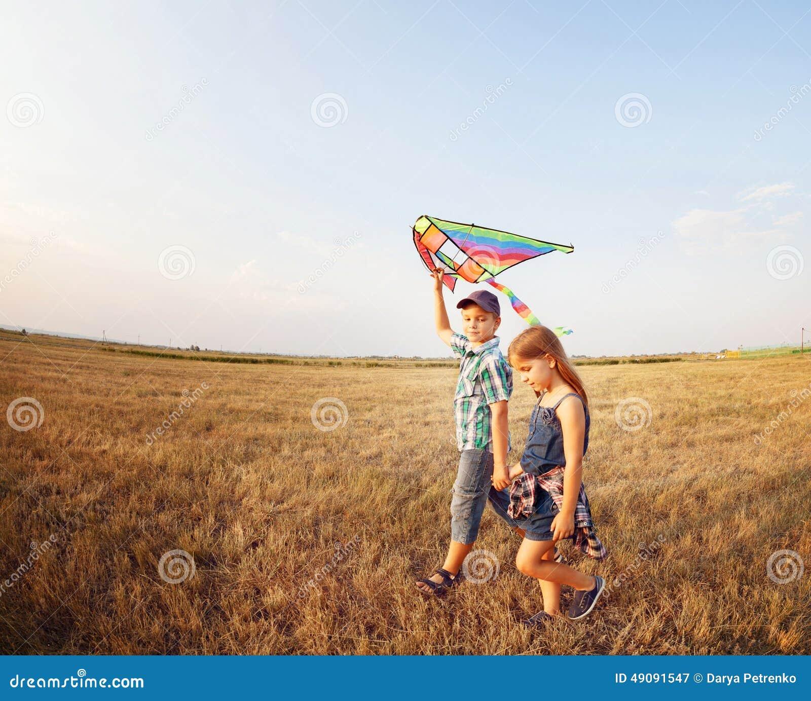 Gelukkig jongen en meisje met heldere vlieger op een weide stock afbeelding afbeelding 49091547 - Twee meisjes en een jongen ...