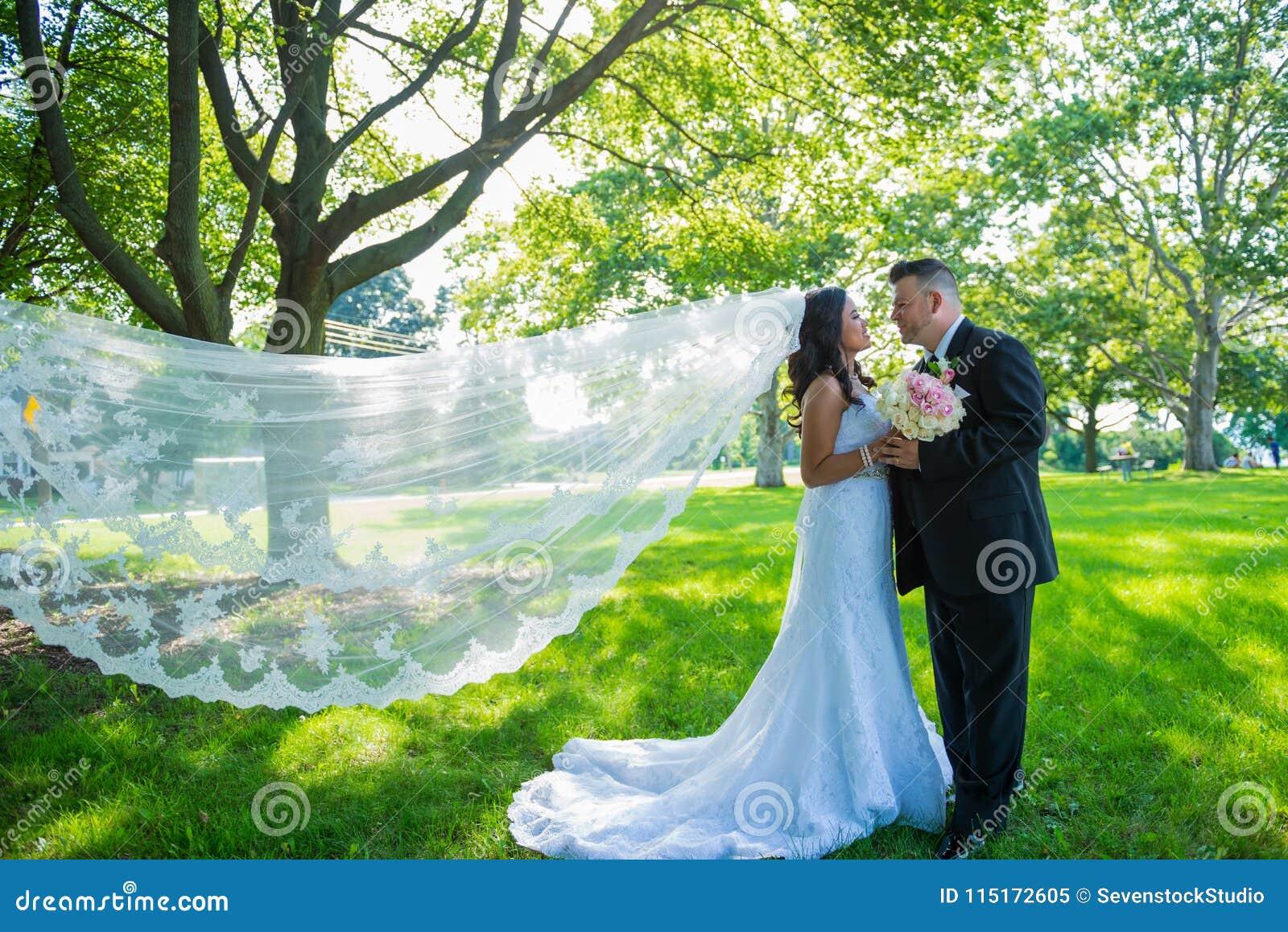 Gelukkig jonggehuwdepaar die elkaar handen houden, bruid en bruidegom die met sluier onder ogen zien die in de wind blazen