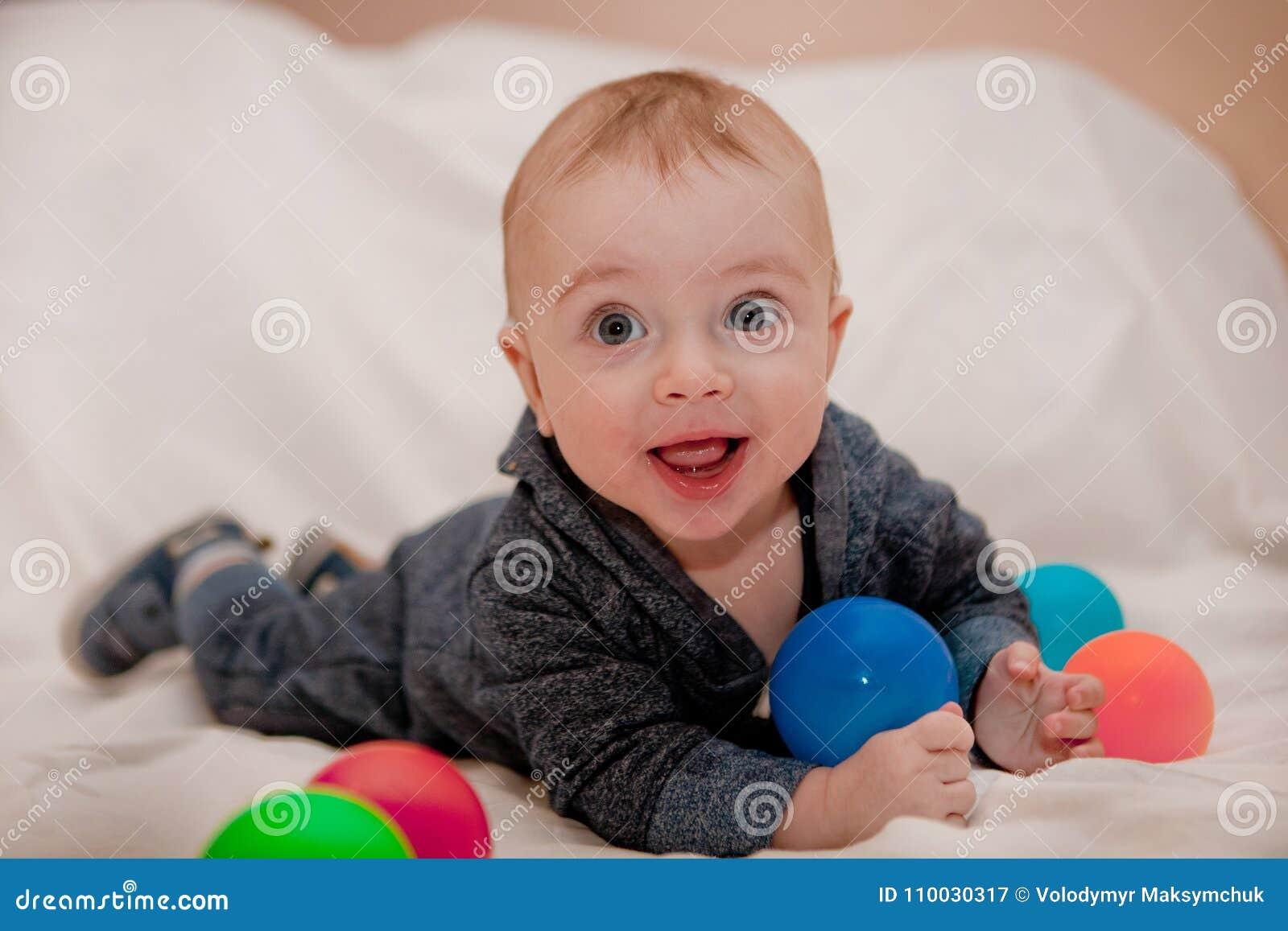 Gelukkig kind die en pret met kleurrijke ballen spelen hebben