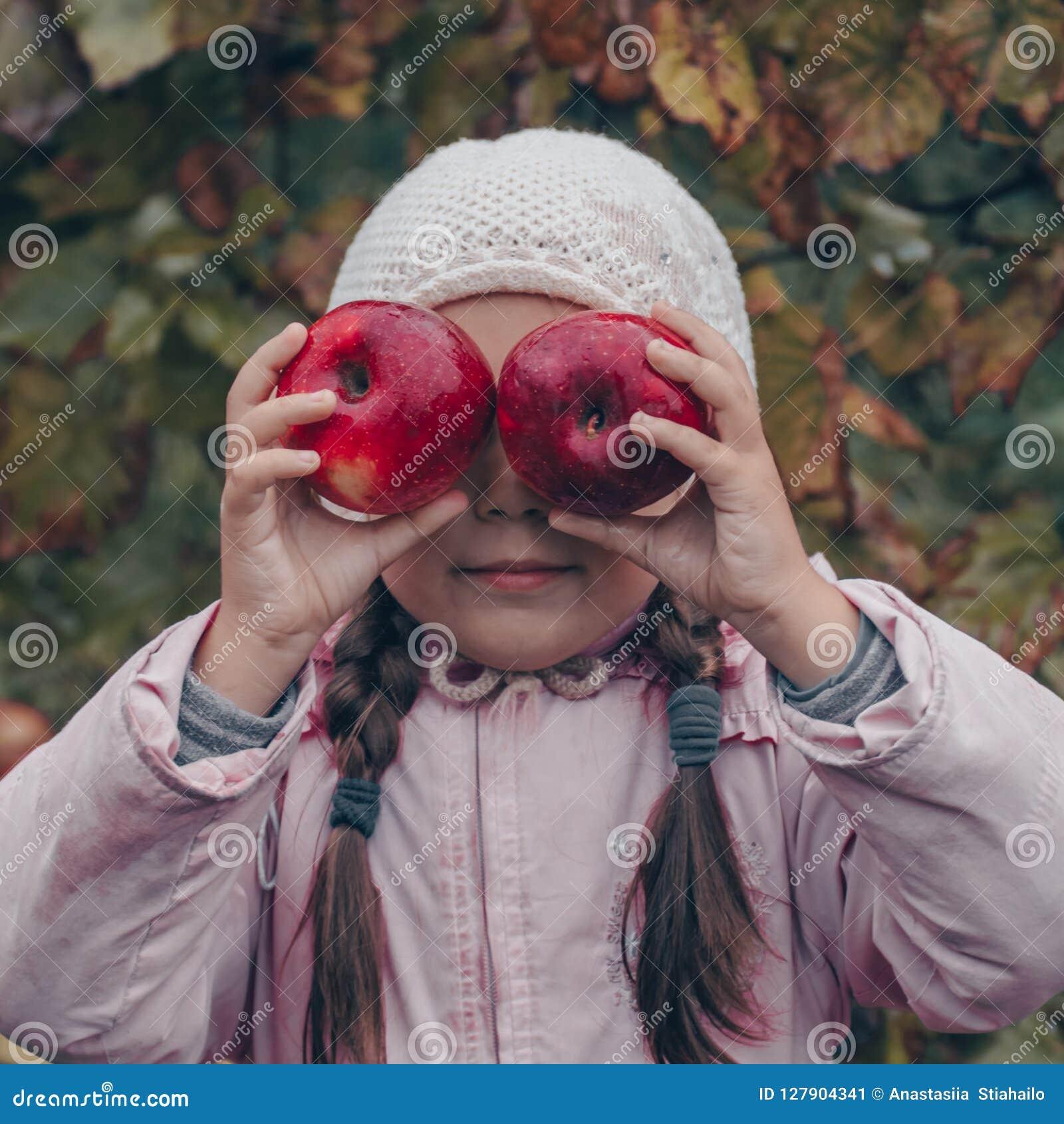 Gelukkig kind die rode appelen in zijn handen houden Oogst Grappig jong geitje in openlucht in de herfstpark