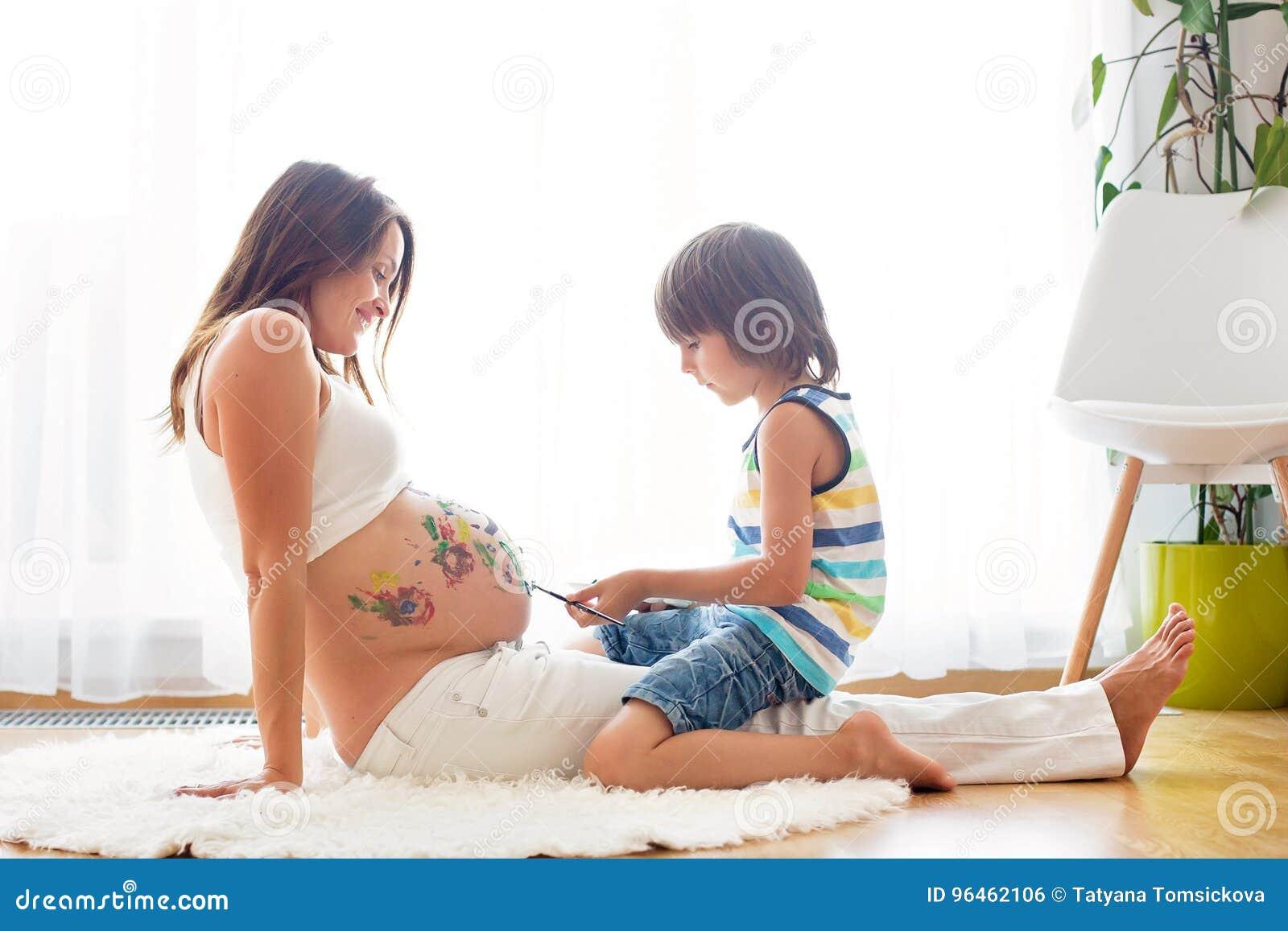Gelukkig kind jongen die op mama` s zwangere buik schilderen