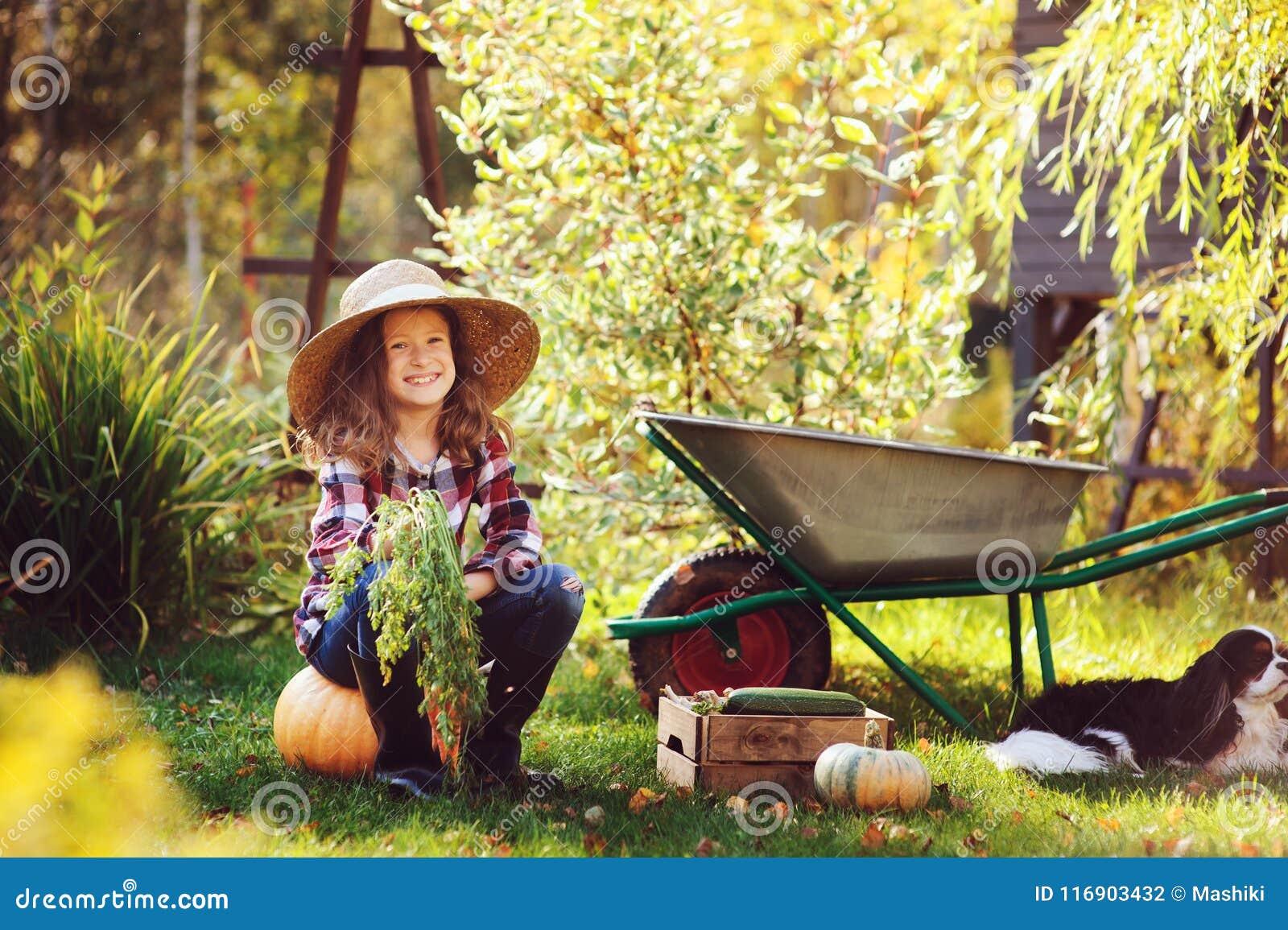 Gelukkig kindmeisje die met spanielhond weinig landbouwer in de herfsttuin spelen
