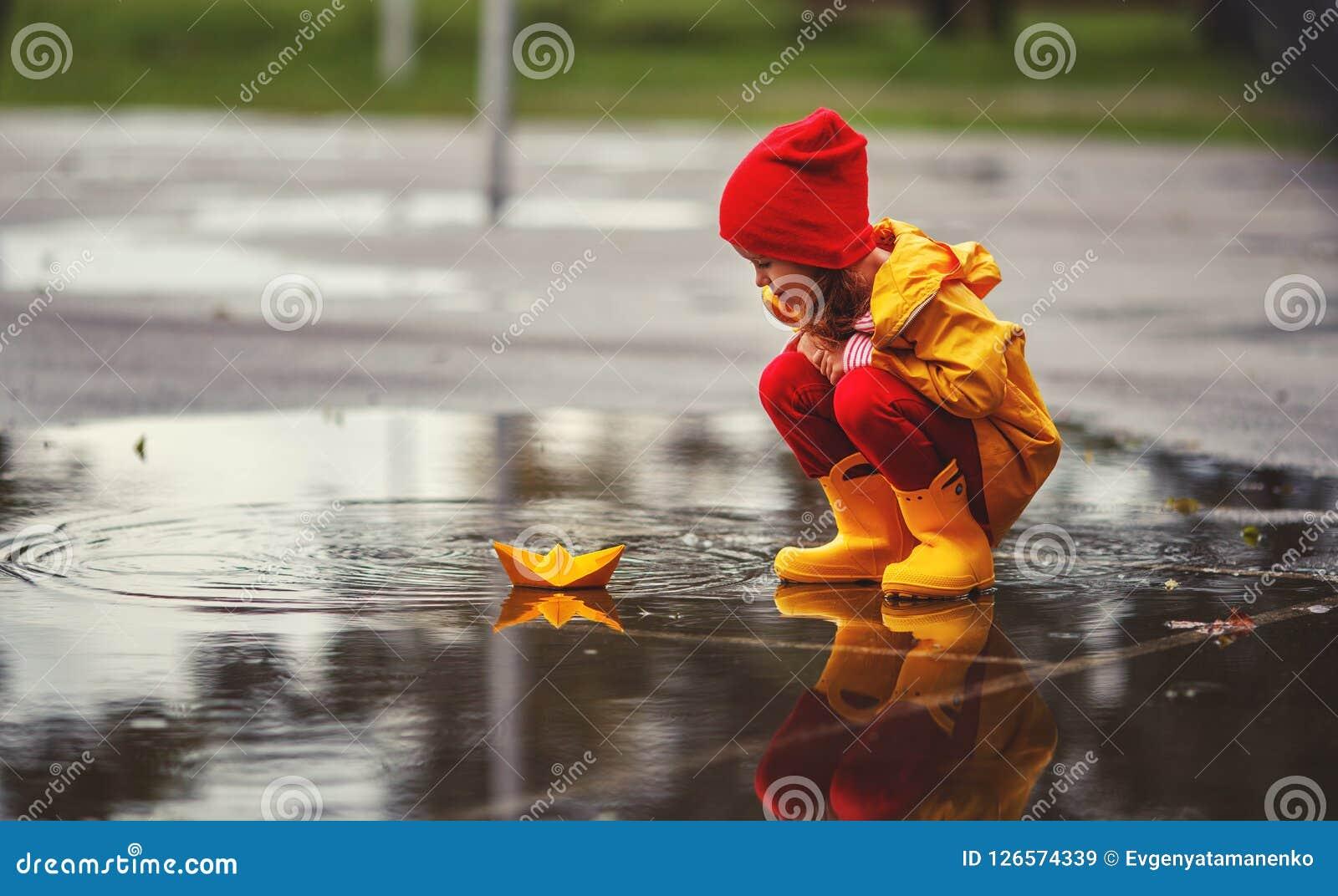 Gelukkig kindmeisje met paraplu en document boot in vulklei in a