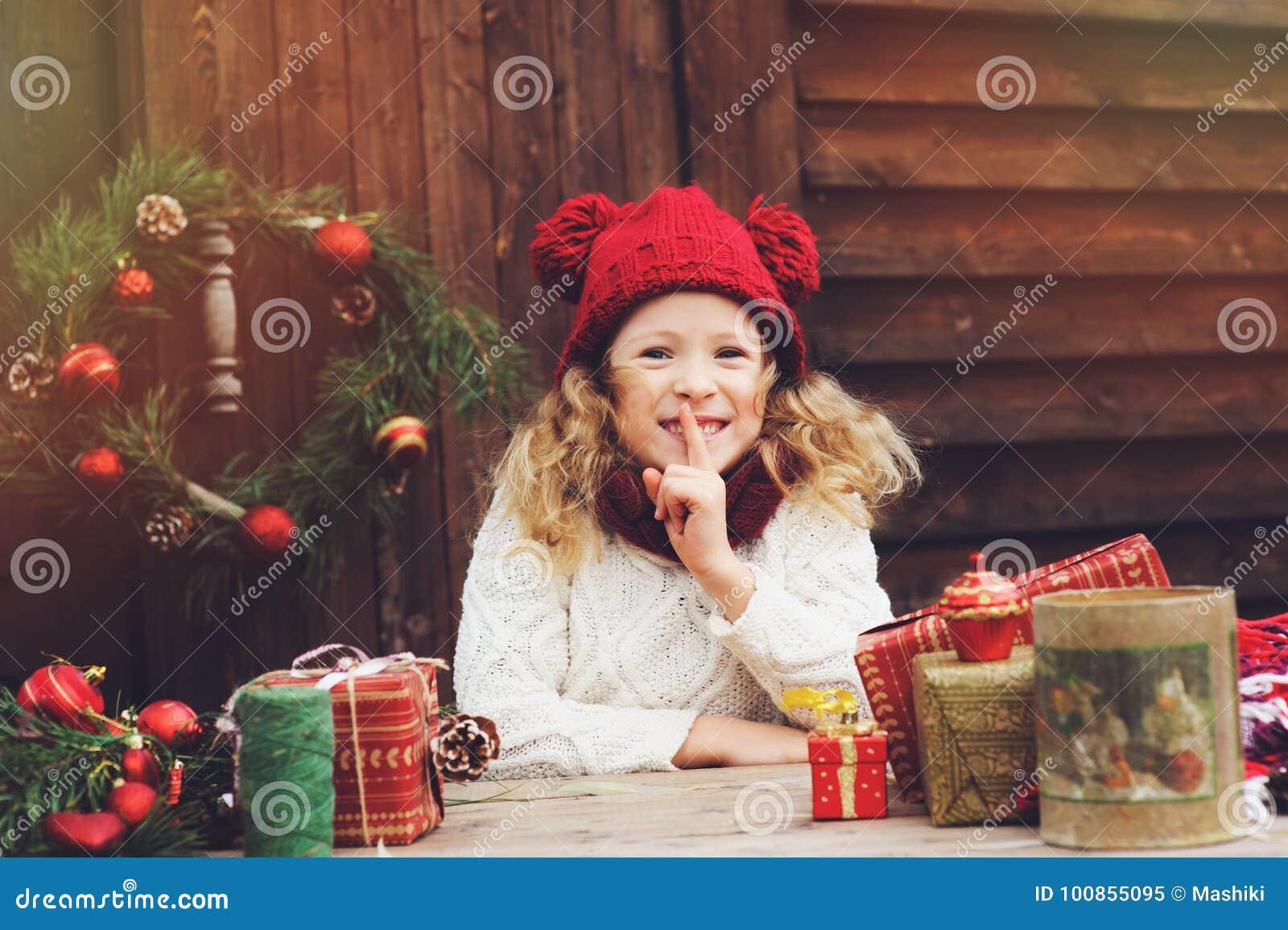 Gelukkig kindmeisje in rode hoed en sjaal verpakkende Kerstmisgiften bij comfortabel buitenhuis, dat voor Nieuwjaar en Kerstmis w