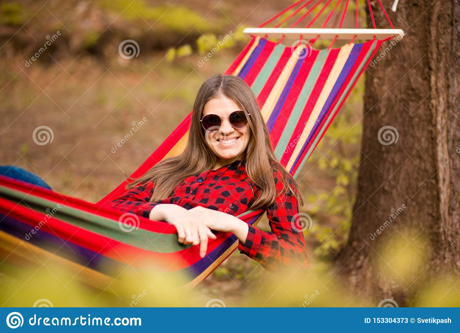 Gelukkig Levensstijlconcept Mooie onbezorgde vrouw in zonnebril in bos die gelukkig in openlucht terwijl rust op hangmat zijn