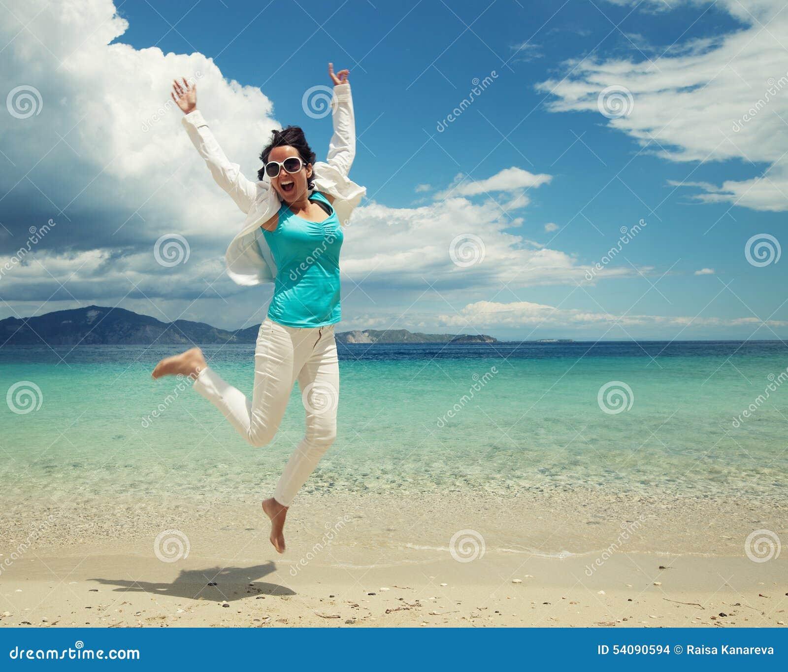 Gelukkig meisje dat op het strand springt