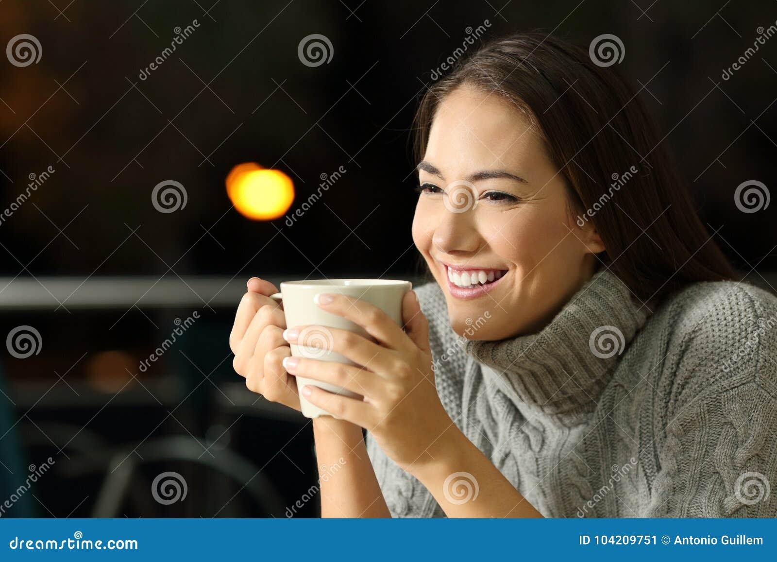 Gelukkig meisje die coffe in de nacht drinken