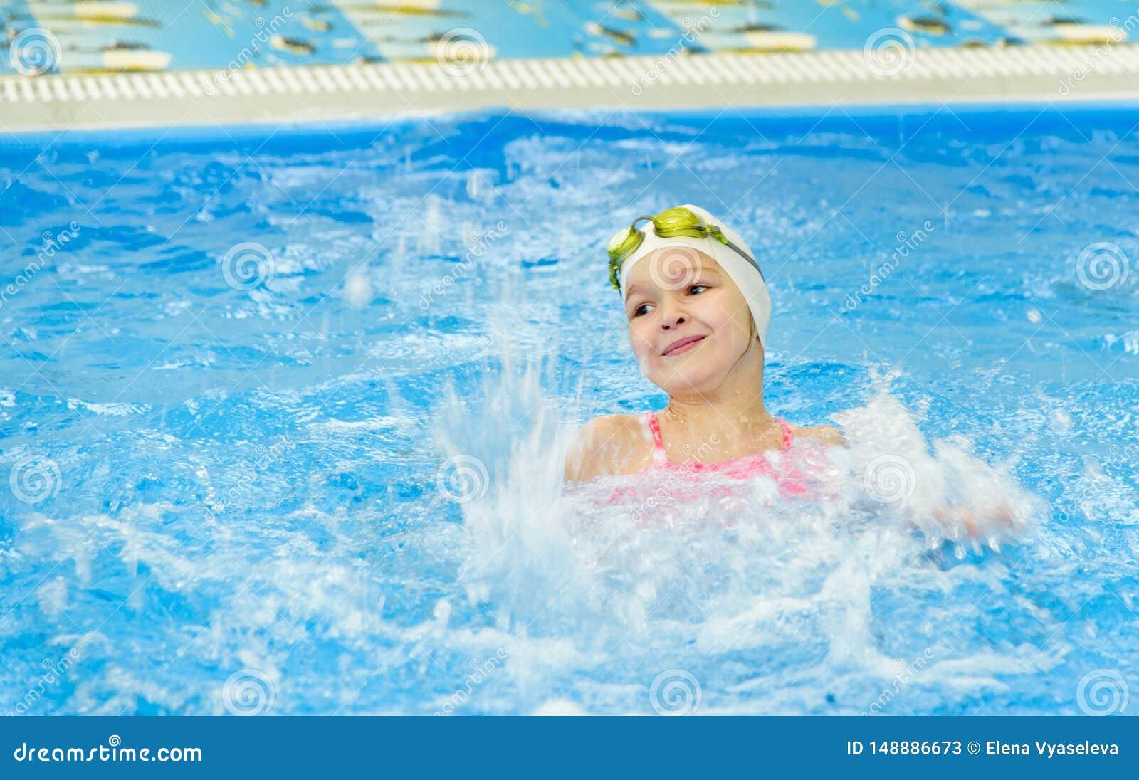Gelukkig meisje die in de pool zwemmen Het Kaukasische kind speelt pret in de kleuterschoolpool