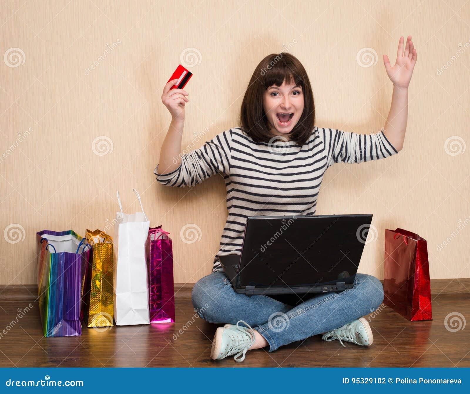 Gelukkig meisje die met het winkelen zakken op de vloer met laptop a zitten