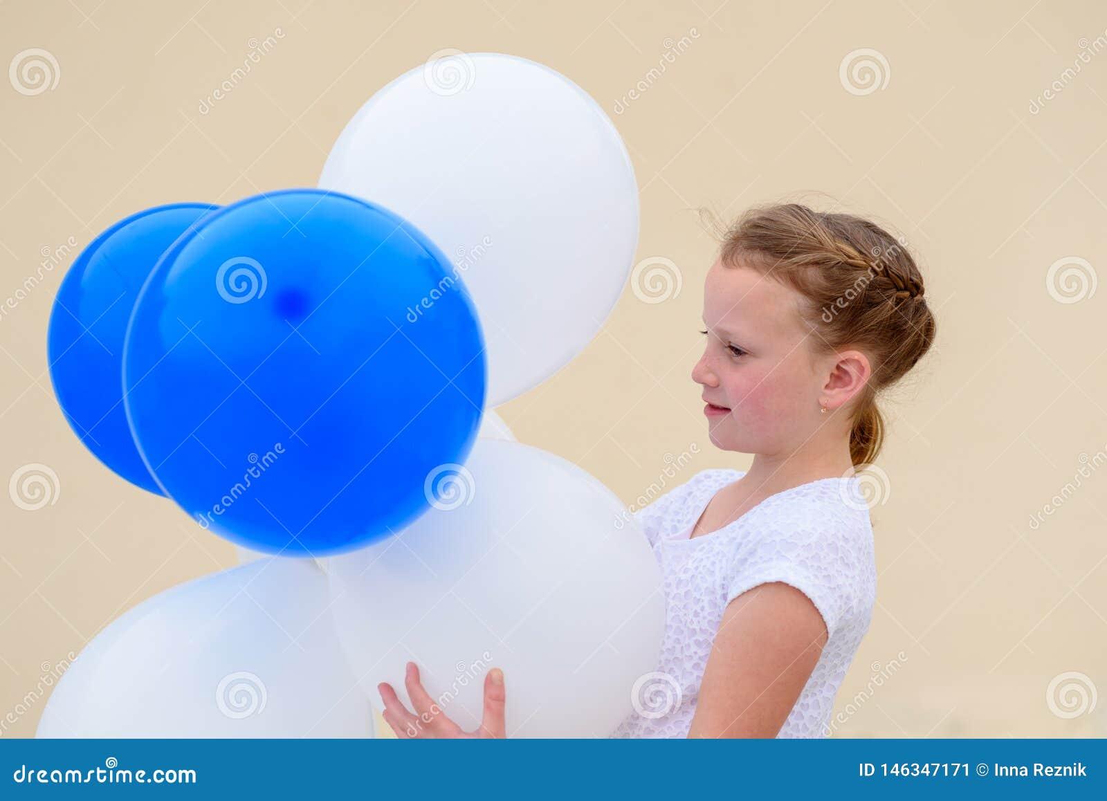 Gelukkig meisje met blauwe en witte ballons