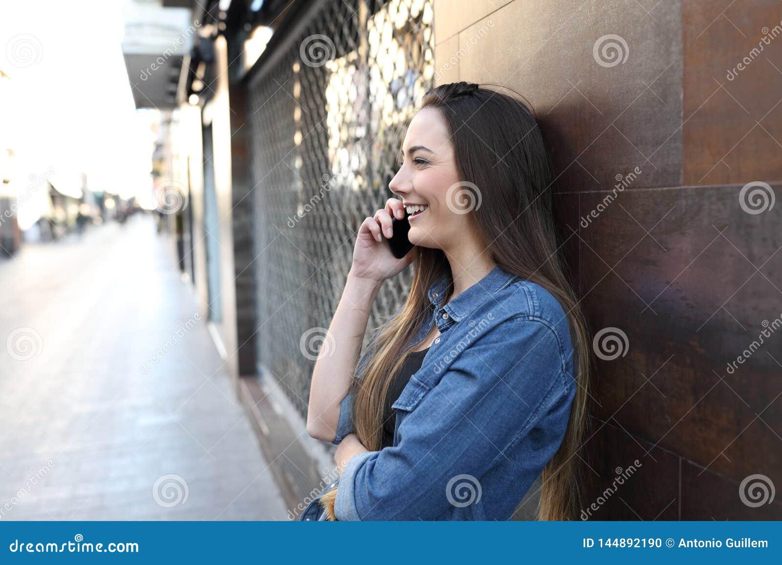 Gelukkig meisjesprofiel dat op telefoon in de straat spreekt