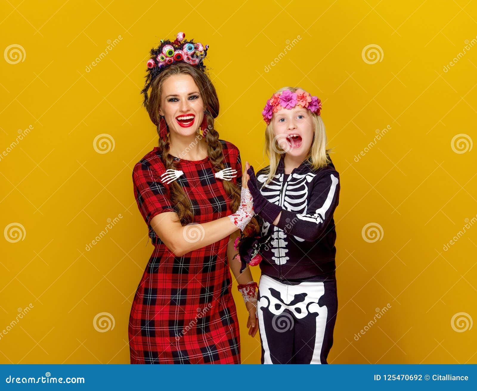 Gelukkig modern moeder en kind in Halloween-kostuum hoge vijf