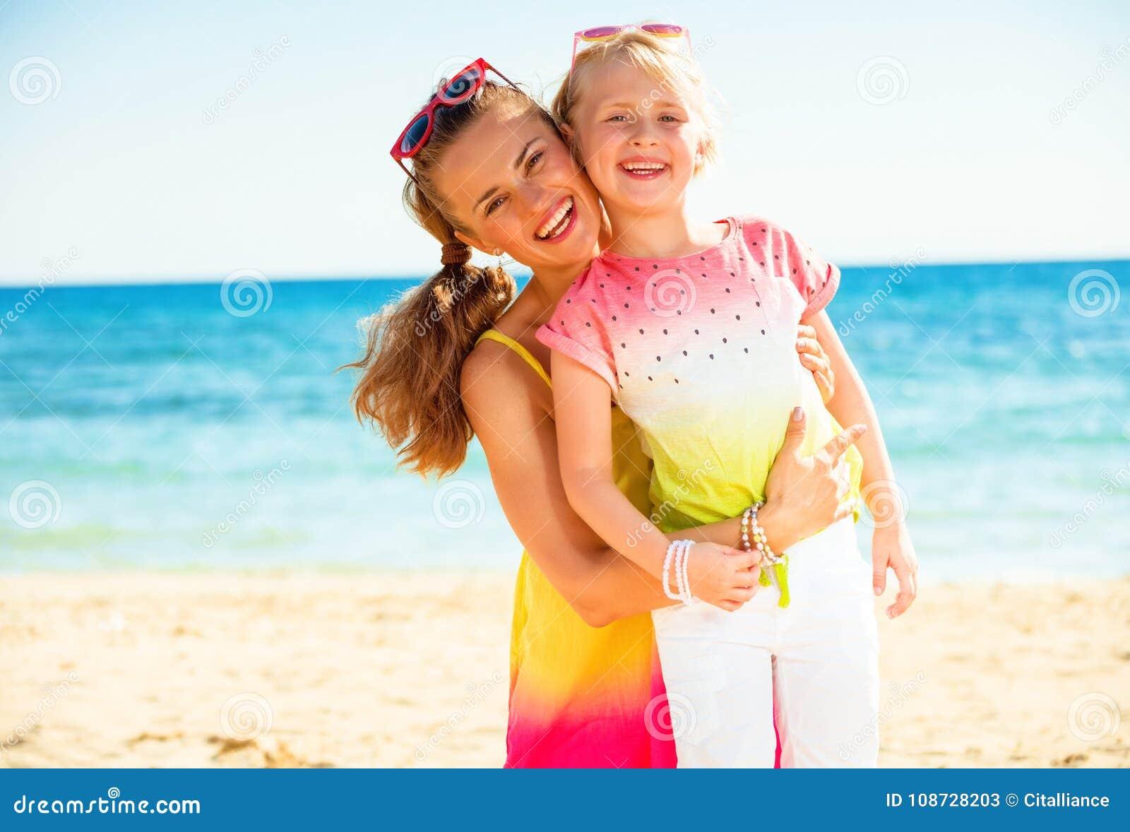Gelukkig in moeder en kind in kleurrijke kleren op zeekust