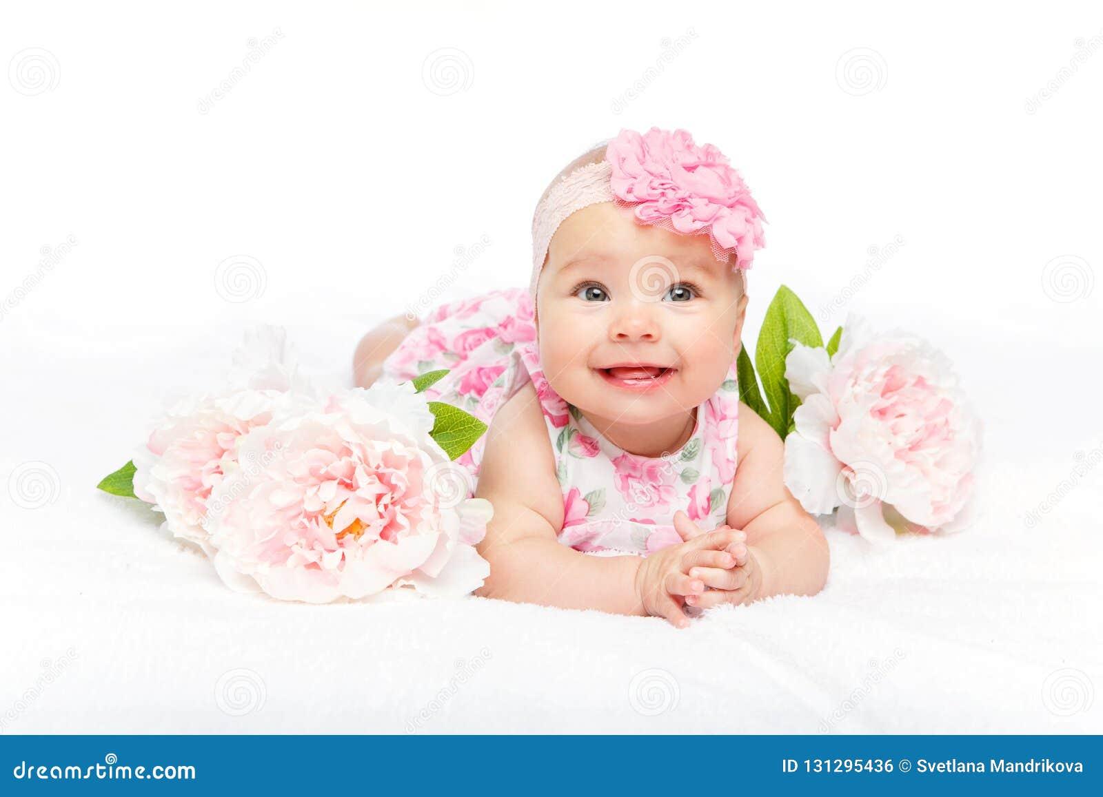 Gelukkig mooi babymeisje met bloem op hoofd