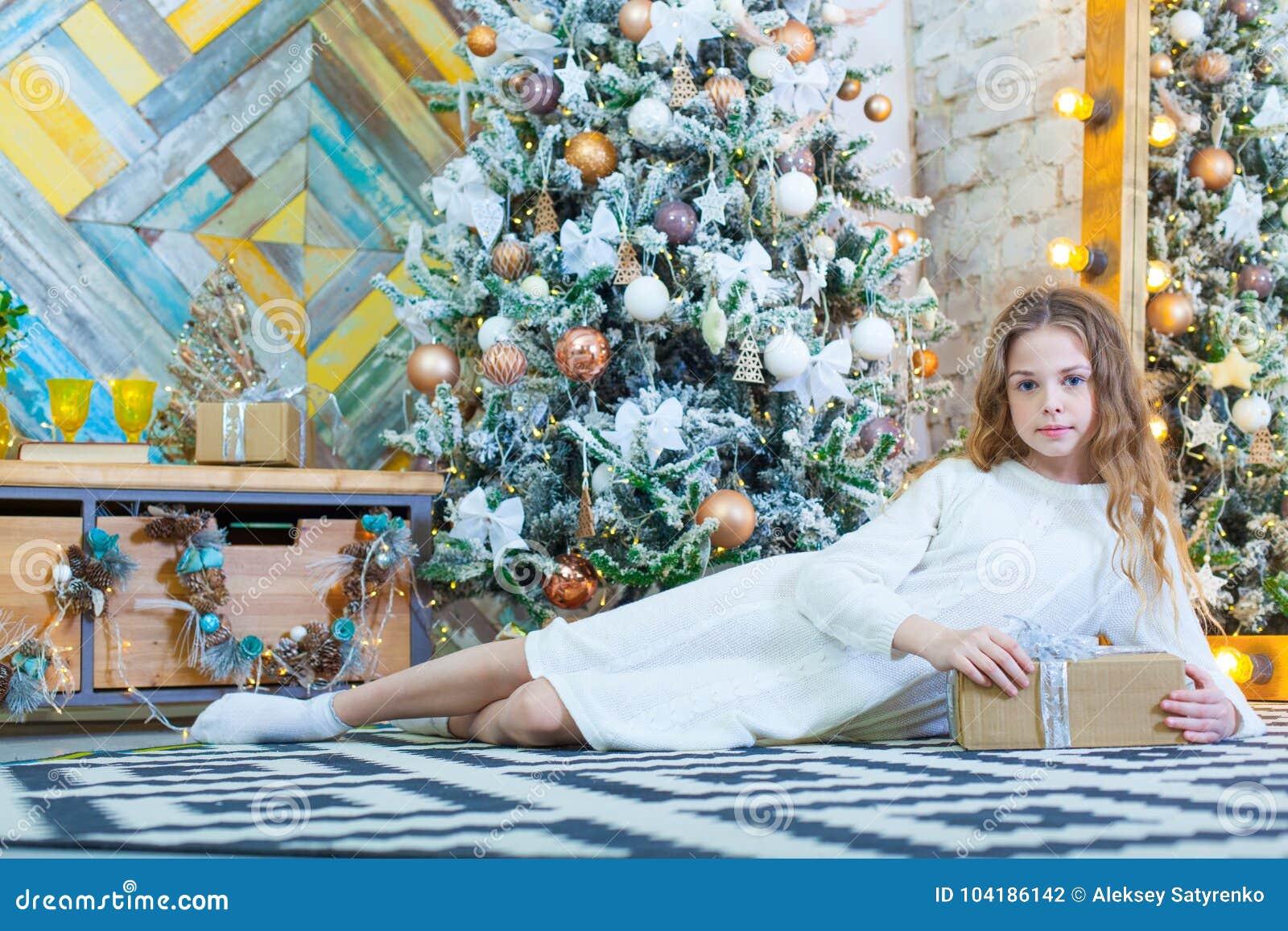 Gelukkig mooi kindmeisje met Kerstmisheden thuis op de vloer