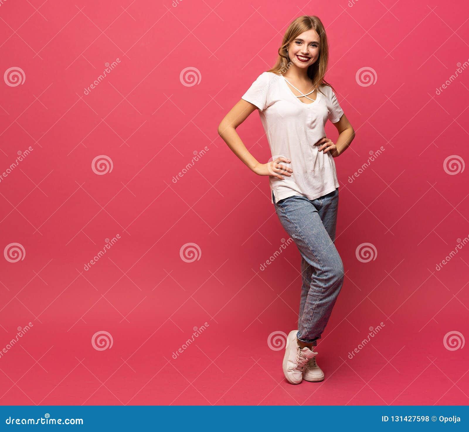 Gelukkig mooi meisje die zich in volledige die lengte bevinden, op roze achtergrond wordt geïsoleerd