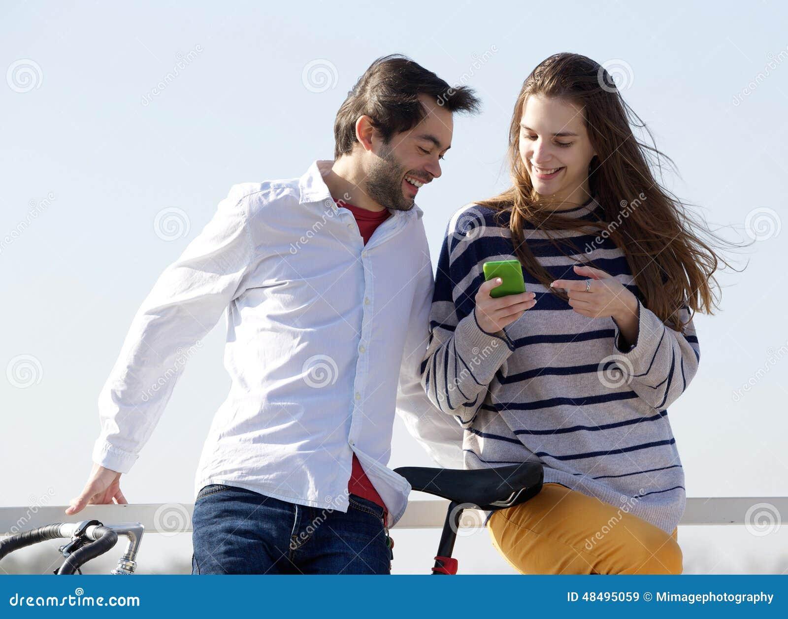 Gelukkig paar buiten het bekijken tekstbericht op celtelefoon