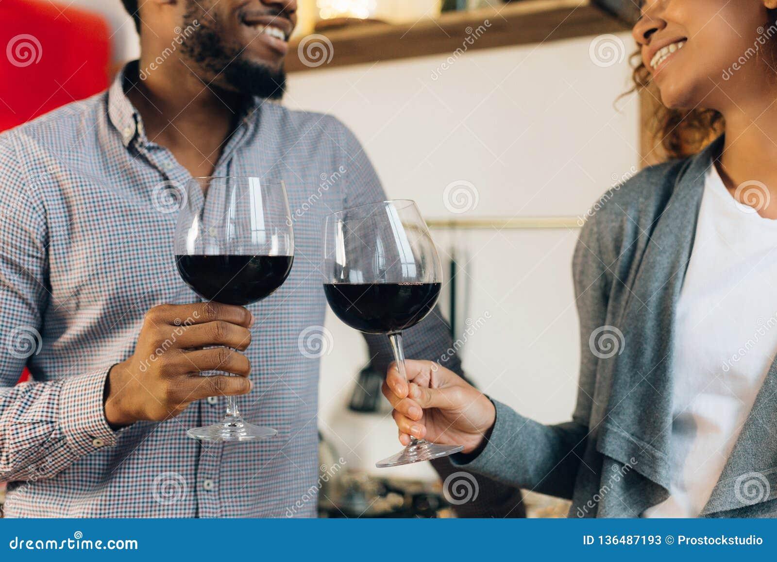 Gelukkig paar die en met glazen wijn vieren toejuichen