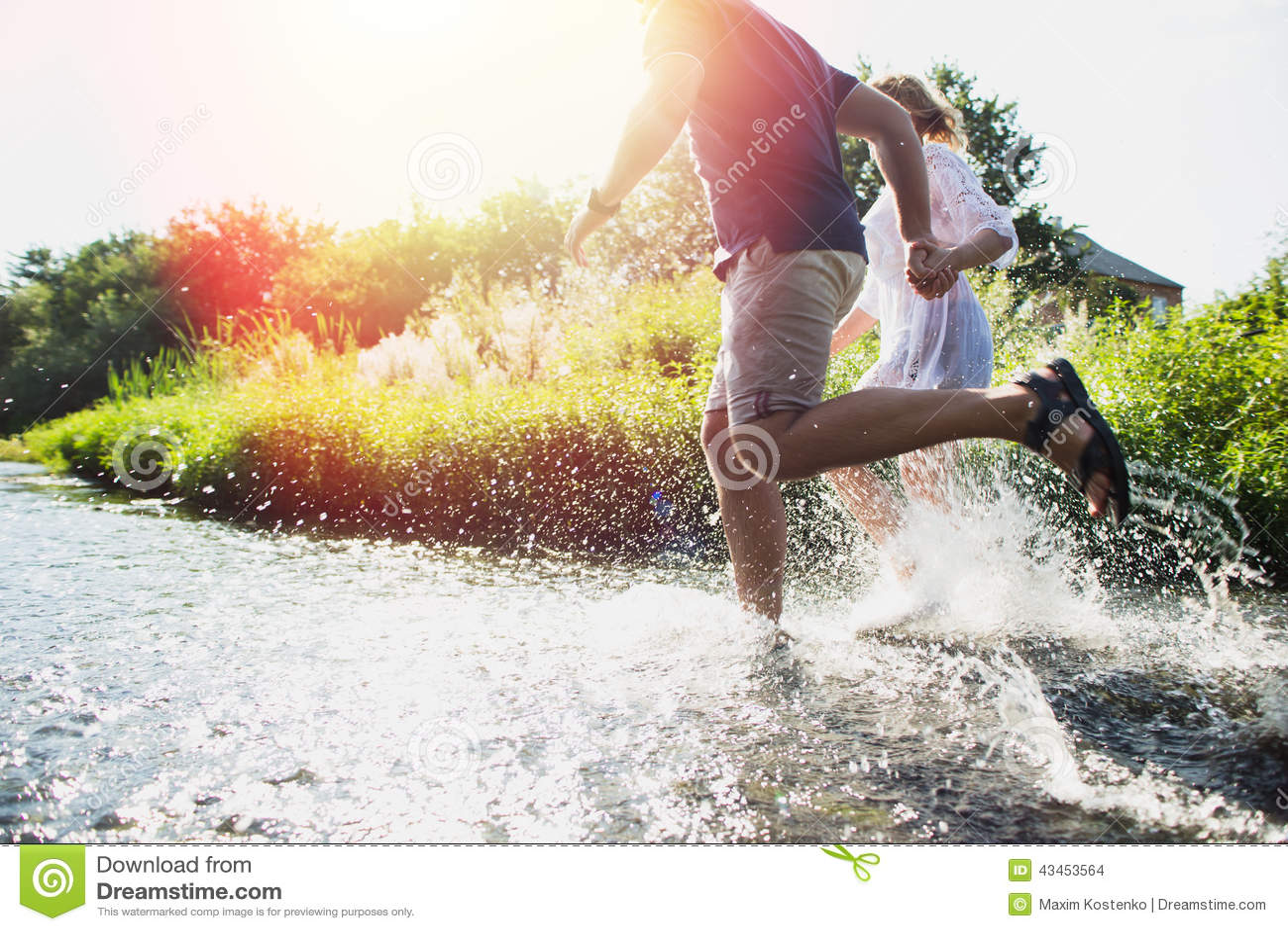 Gelukkig paar die in ondiep water lopen