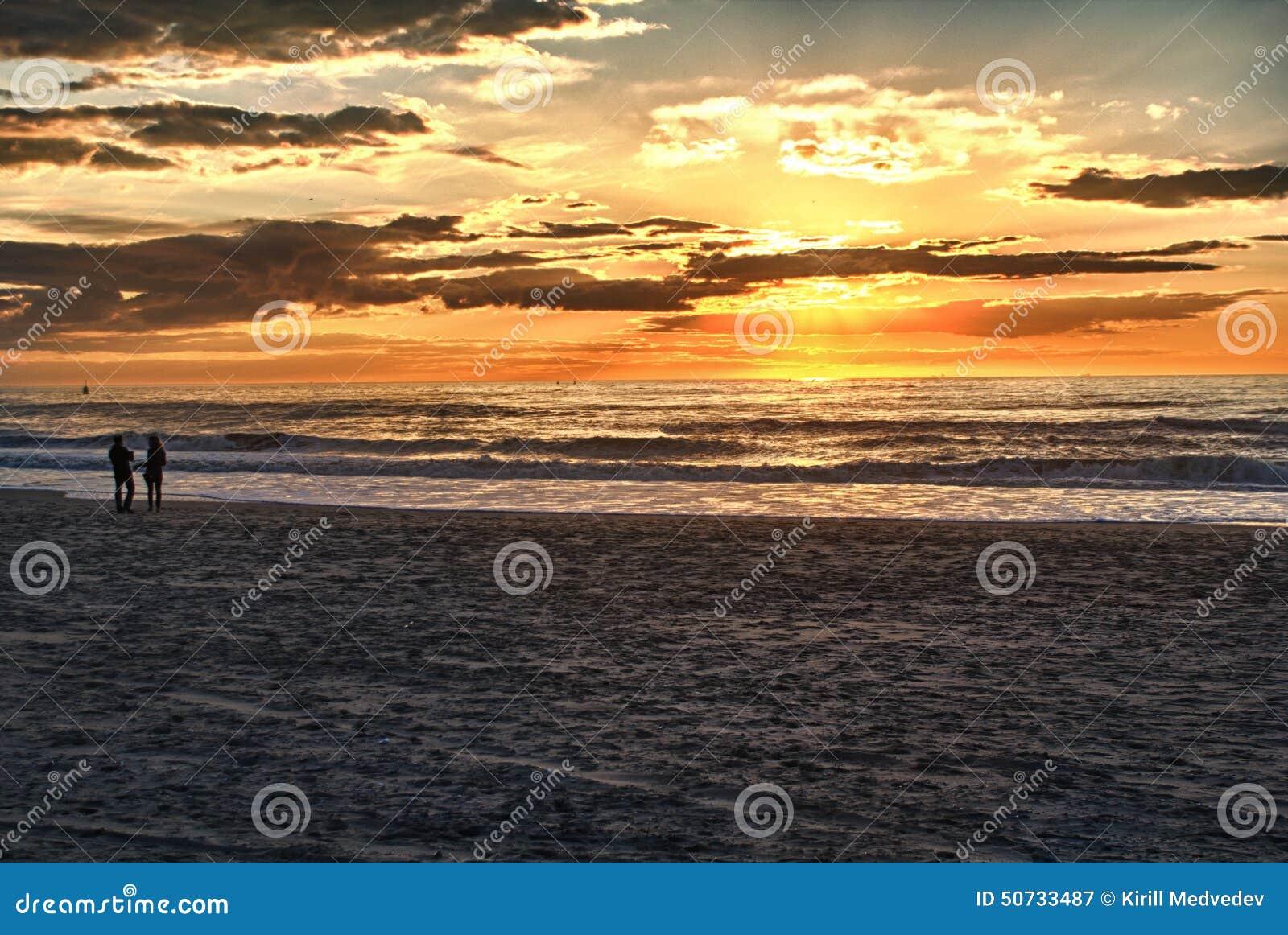Gelukkig paar die op het strand bij zonsopgang voor vakantietijd lopen