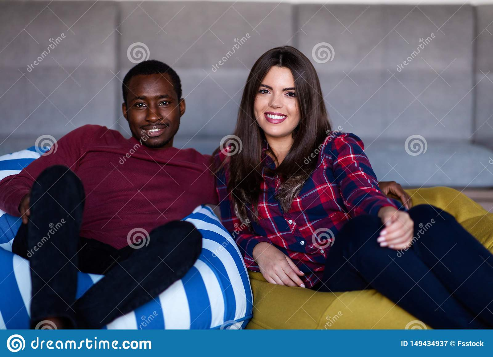 Gelukkig paar met computertablet en smartphone op een bank