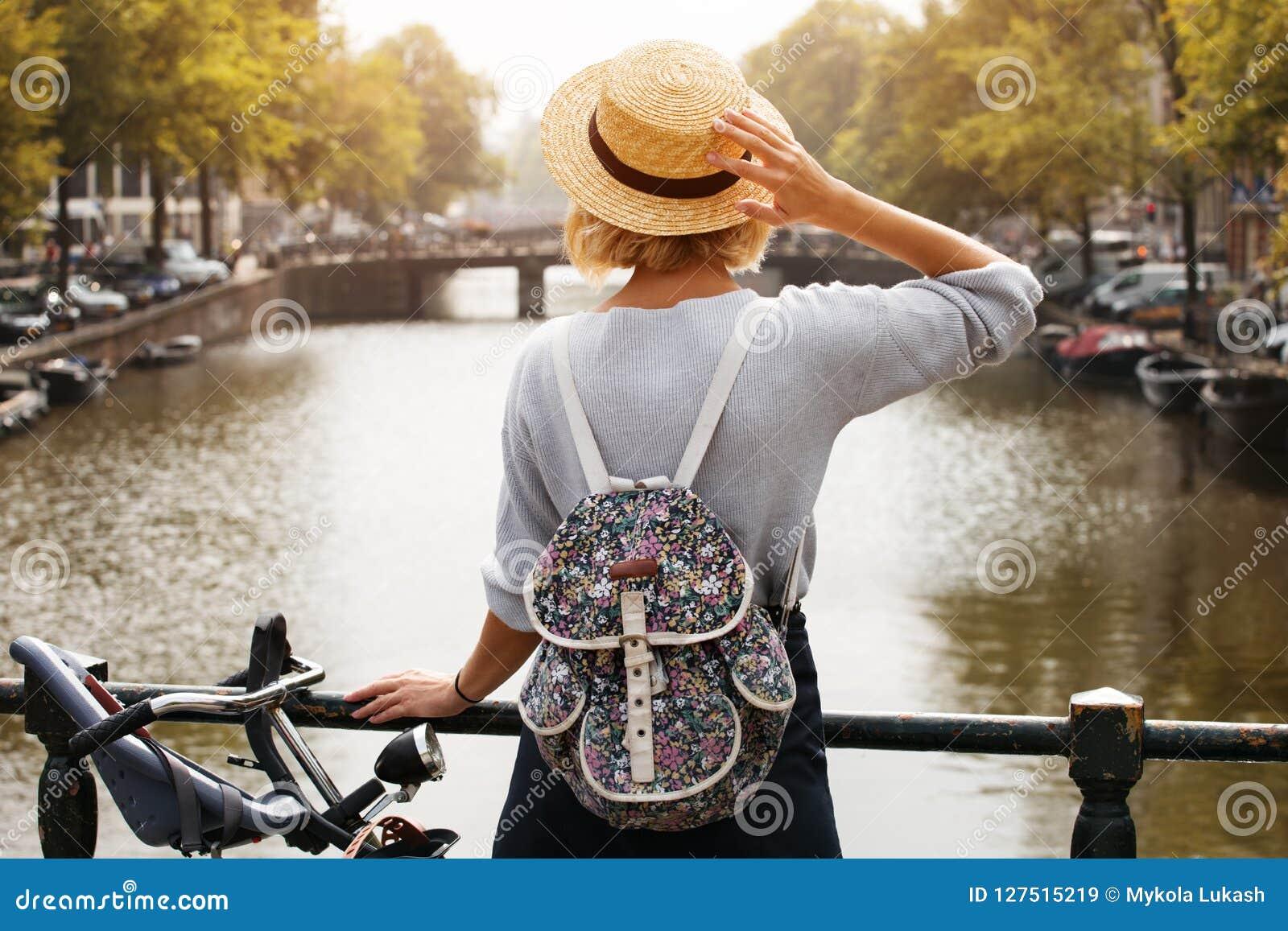 Gelukkig reizigersmeisje die van de stad van Amsterdam genieten Toeristenvrouw die aan het kanaal van Amsterdam, Nederland, Europ