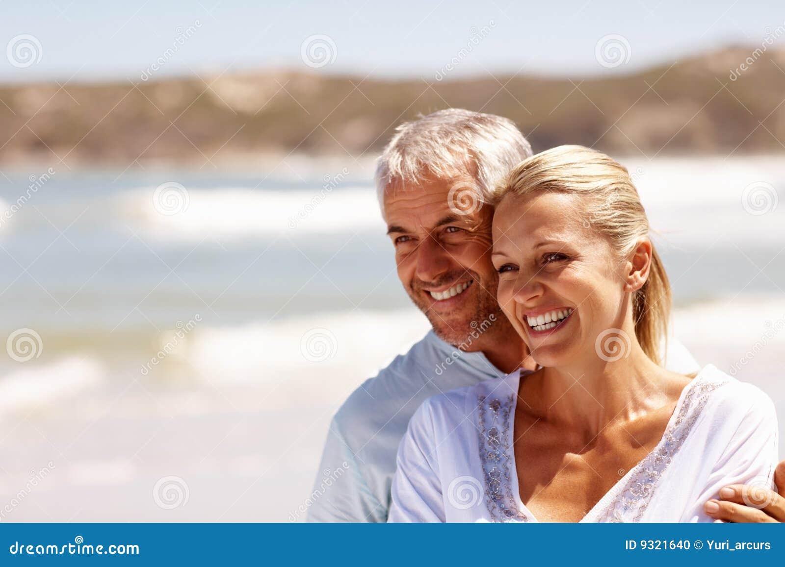 Gelukkig rijp paar dat bij het strand omhelst