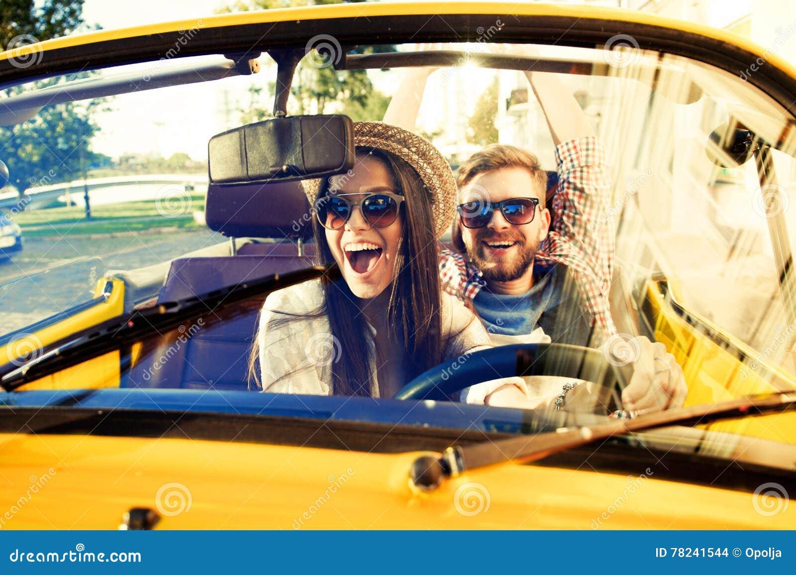 Gelukkig samen te reizen Blij jong paar die terwijl het berijden in onvertible glimlachen
