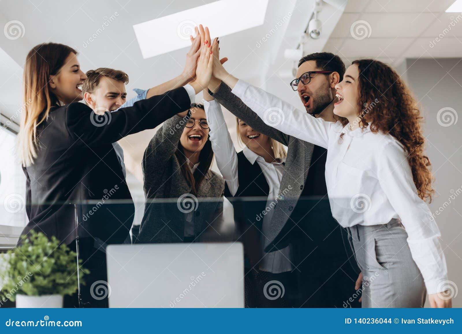 Gelukkig succesvol multiraciaal commercieel team die een hoog fivesgebaar geven aangezien zij lachen en hun succes toejuichen