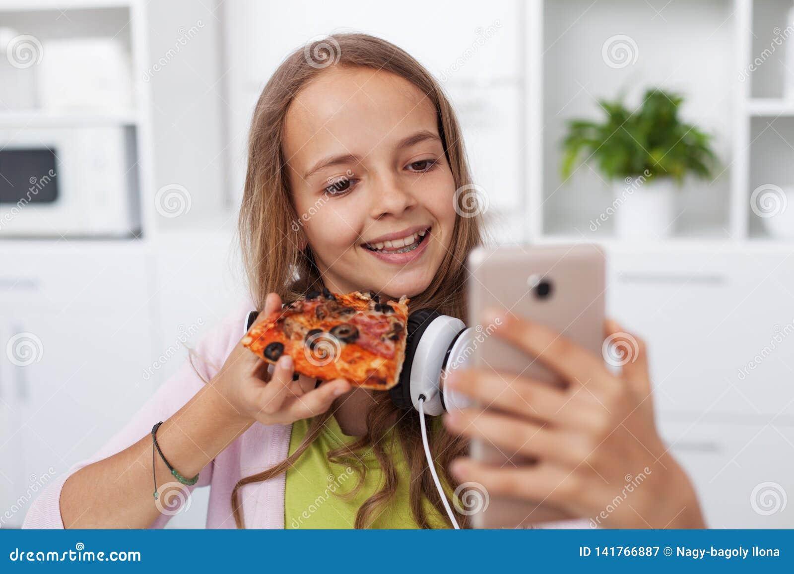 Gelukkig tienermeisje die een selfie in keuken het stellen met een plak van pizza nemen