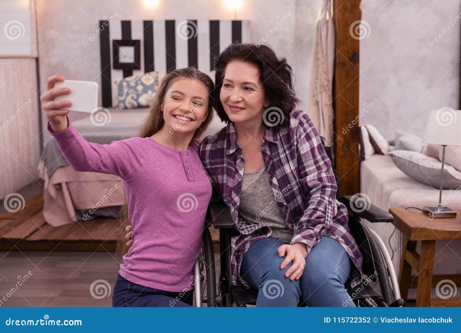 Gelukkig verlamd vrouw en meisje die foto nemen