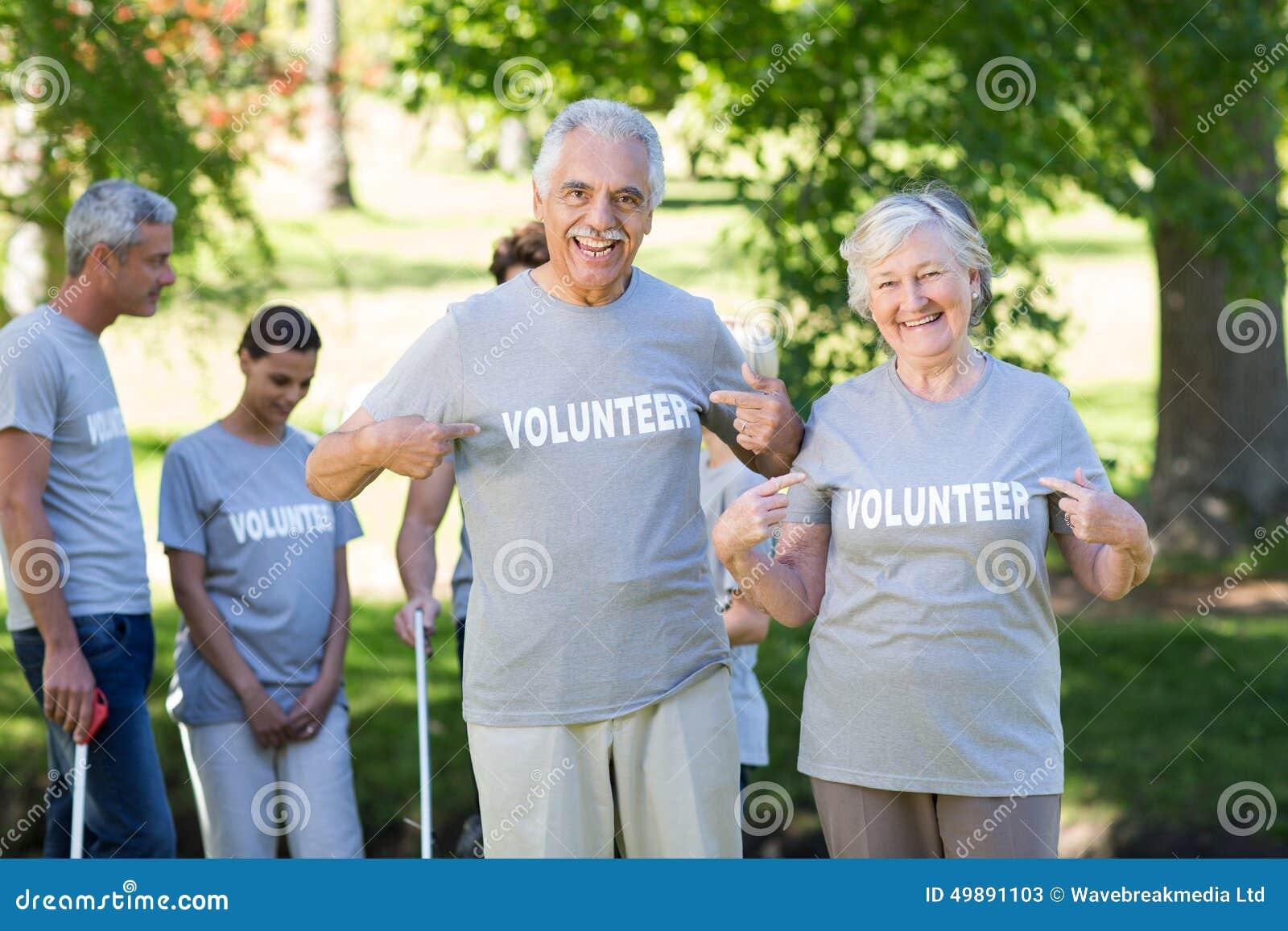 Gelukkig vrijwilligers hoger paar die bij de camera glimlachen