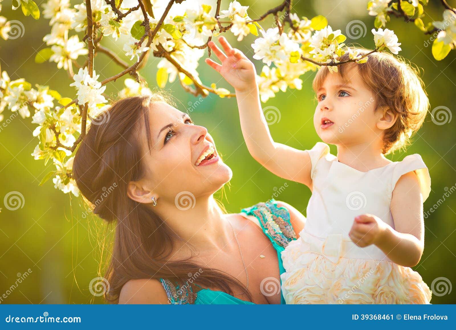 Gelukkig vrouw en kind in de bloeiende de lentetuin. Kindkissi