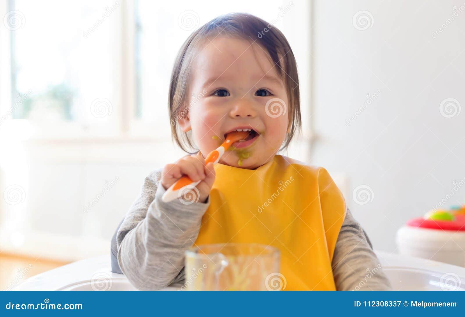 Gelukkig weinig babyjongen die voedsel eten