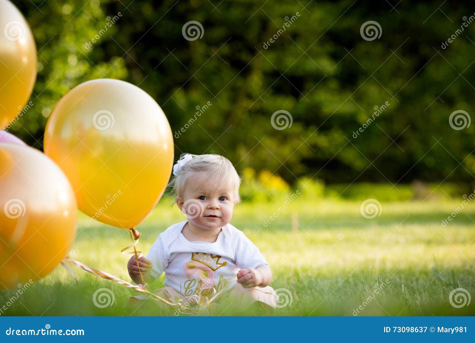 Gelukkig weinig blonde Kaukasisch meisje buiten met ballons