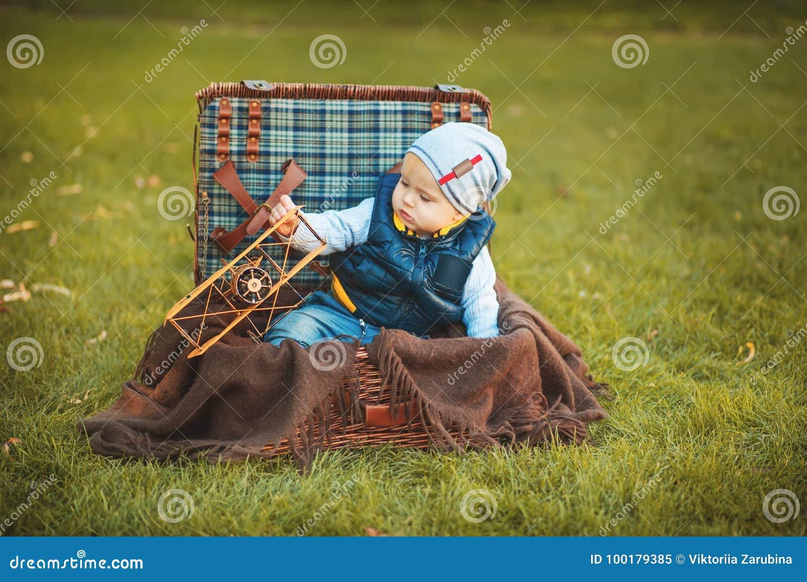 Gelukkig weinig jong geitjejongen die met vliegtuigstuk speelgoed spelen terwijl het zitten in koffer op groen de herfstgazon Kin