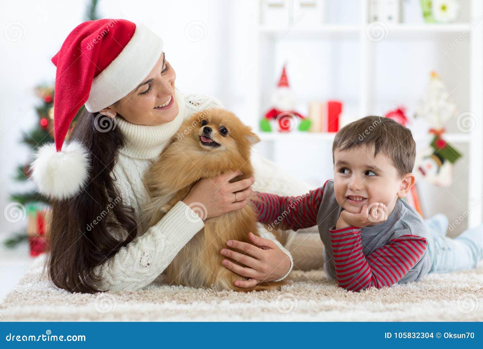 Gelukkig weinig jong geitjejongen, moeder en hond bij Kerstmis