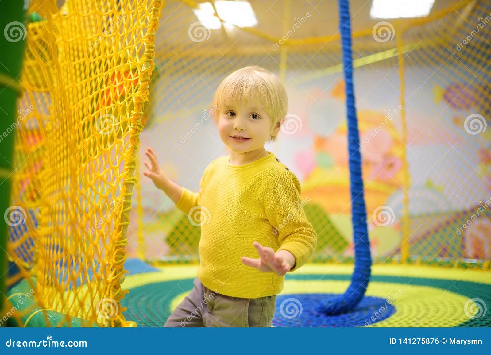 Gelukkig weinig jongen die pret in vermaak in spelcentrum hebben Kind het spelen op binnenspeelplaats