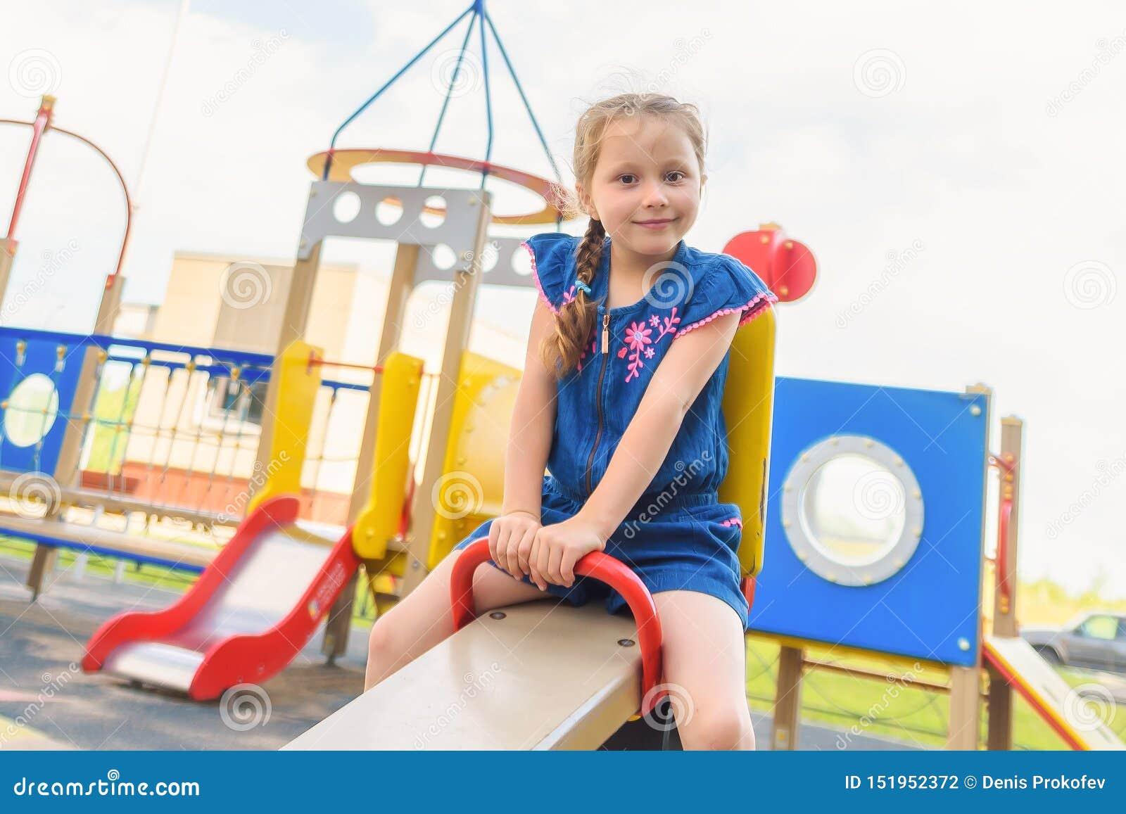 Gelukkig weinig kindmeisje die en op een schommeling in het stadspark lachen slingeren in de zomer