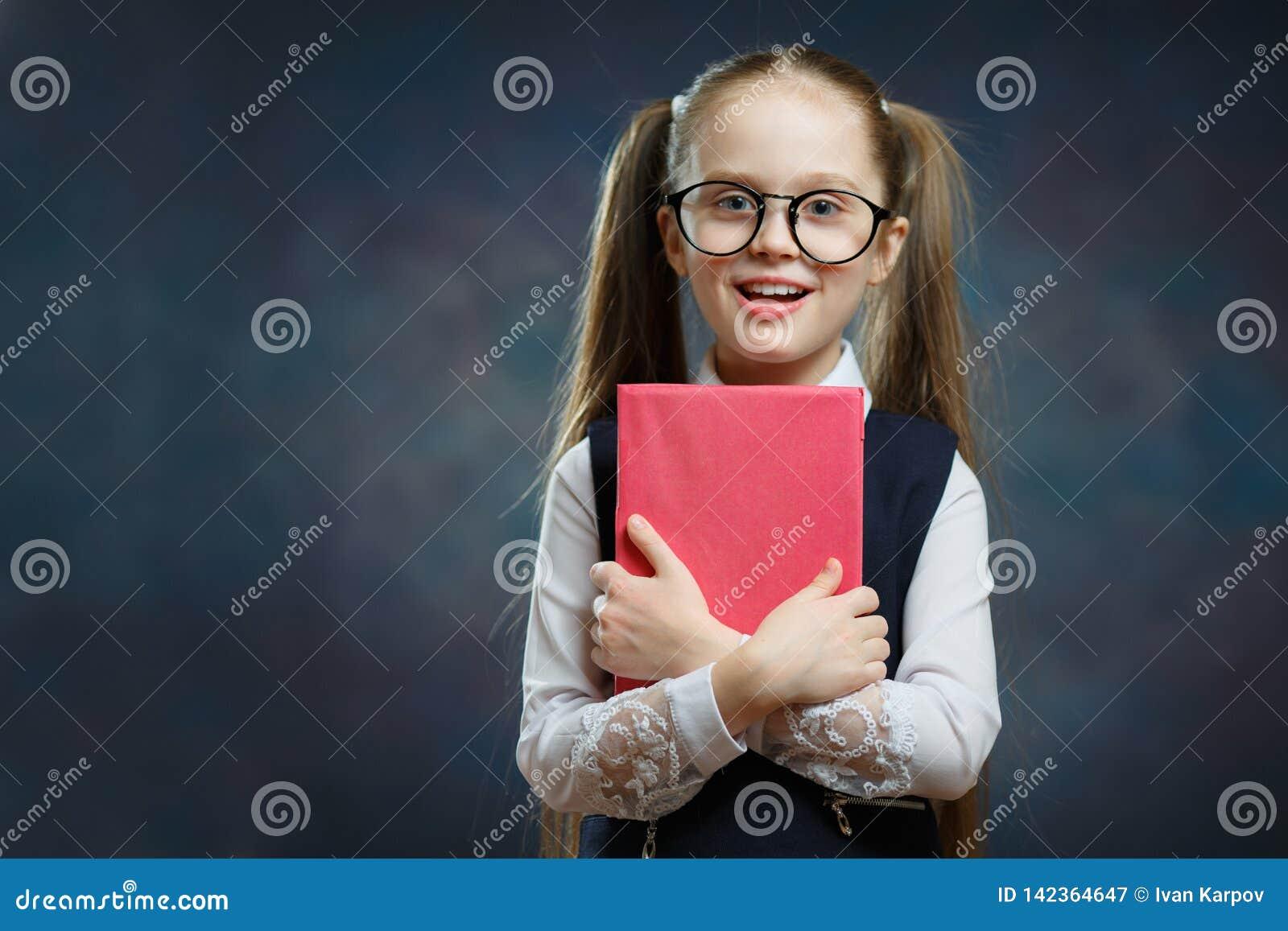 Gelukkig Weinig Schoolmeisje in Eenvormig Greepboek vast