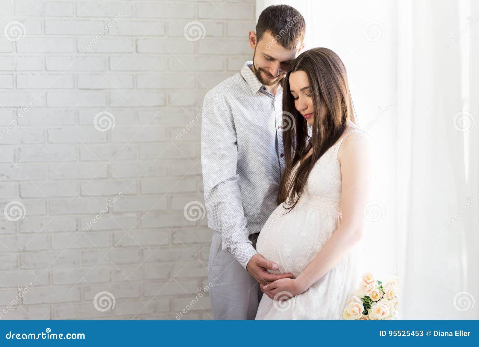 Gelukkig zwanger paar voor het venster