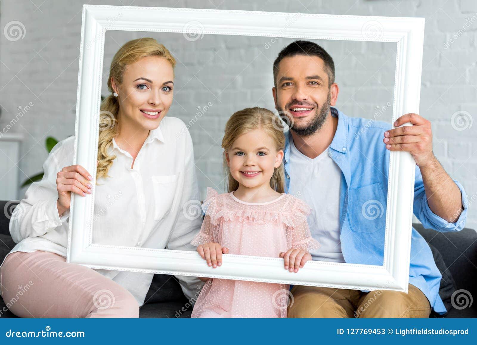 Gelukkige aanbiddelijke ouders met weinig dochter die het witte kader en glimlachen houden
