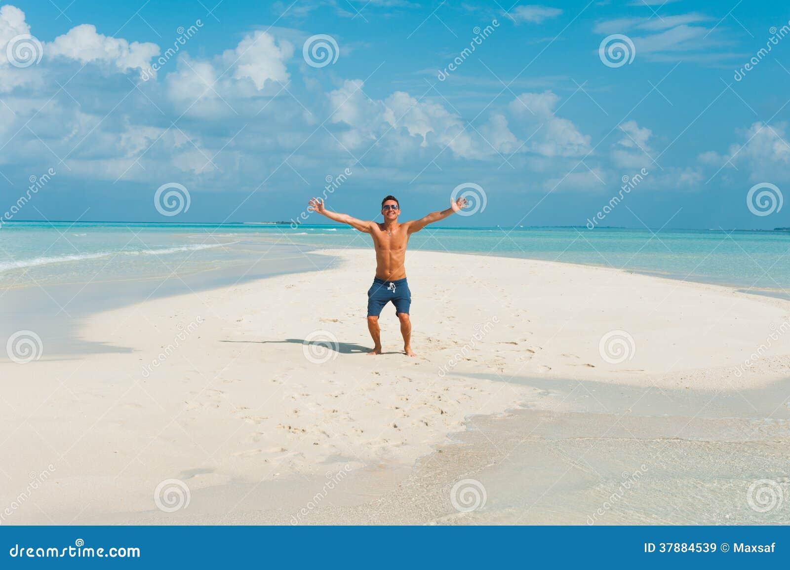 Gelukkige aantrekkelijke jonge mannelijke sprongen op strand met wit zand en o